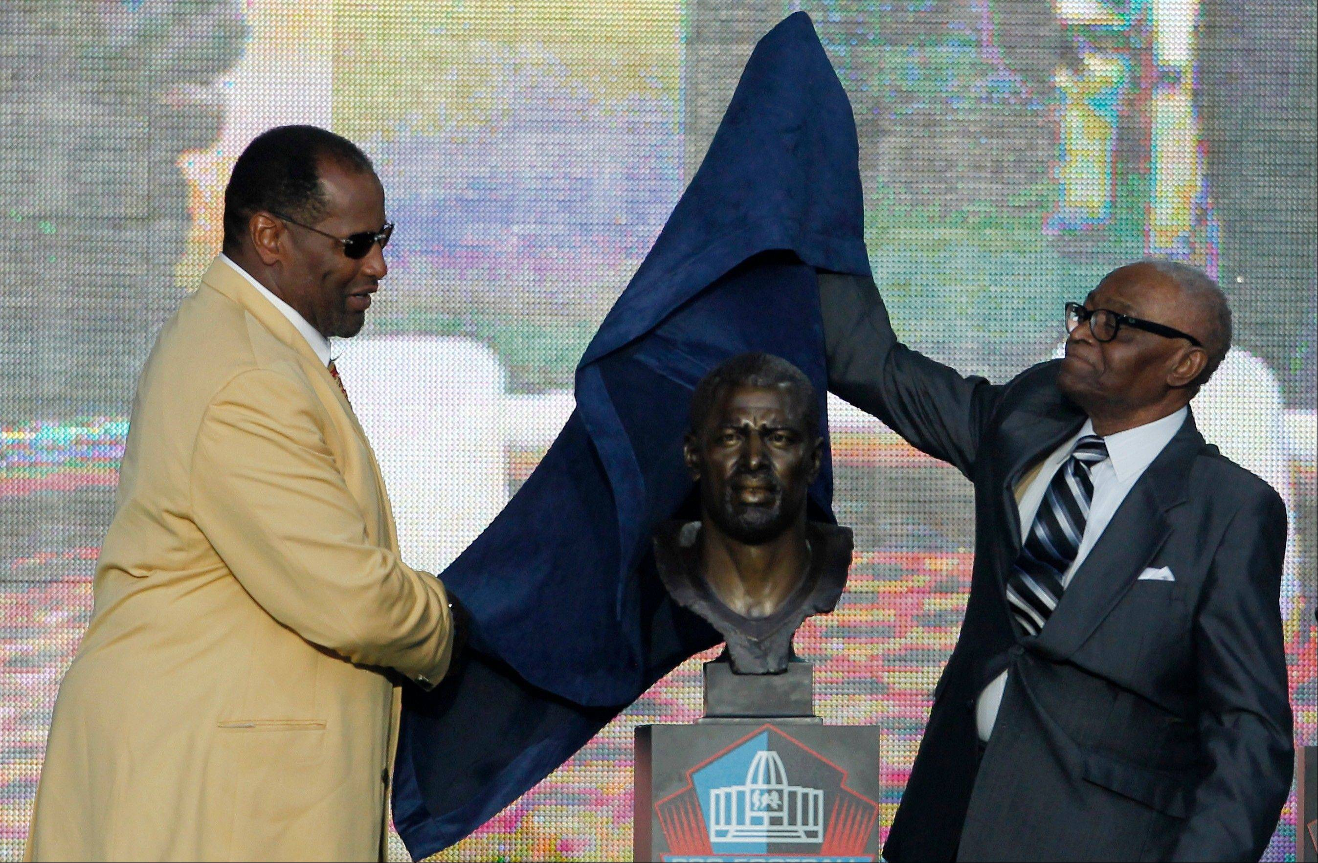 Richard Dent, left, looks on as his presenter, Joe Gilliam, unveils a bust of Dent during Dent's induction ceremony at the Pro Football Hall of Fame on Saturday in Canton, Ohio. Gilliam is a former Tennessee State coach.
