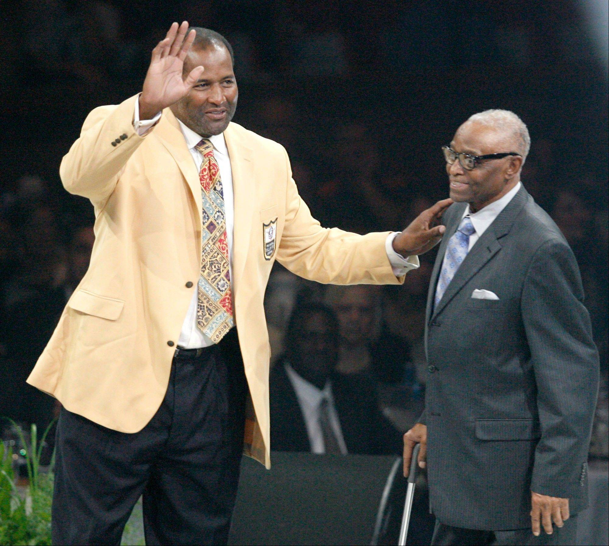 Richard Dent waves to the crowd after receiving his gold jacket from Joe Gilliam at the Pro Football Hall of Fame Festival inductees dinner Friday.