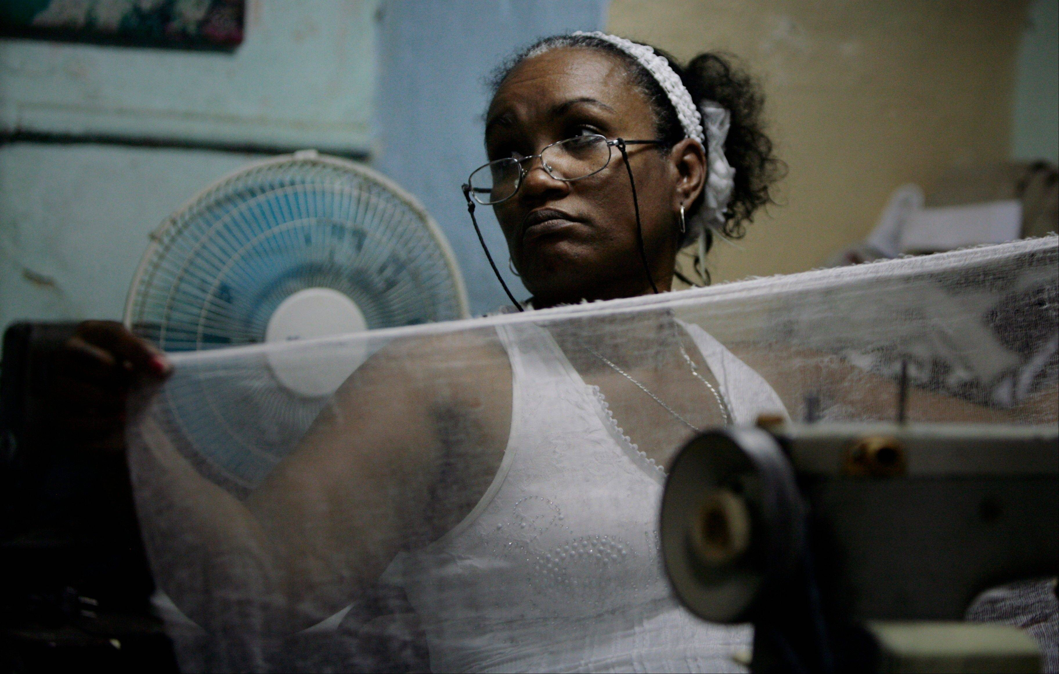 Seamstress Anisia Cardenas works on her sewing machine in Havana. She had set up a stall in a neighbor's patio that she rented for $2 a day. Unable to meet costs, she says she gave up on the stall in March and now works out of her kitchen.