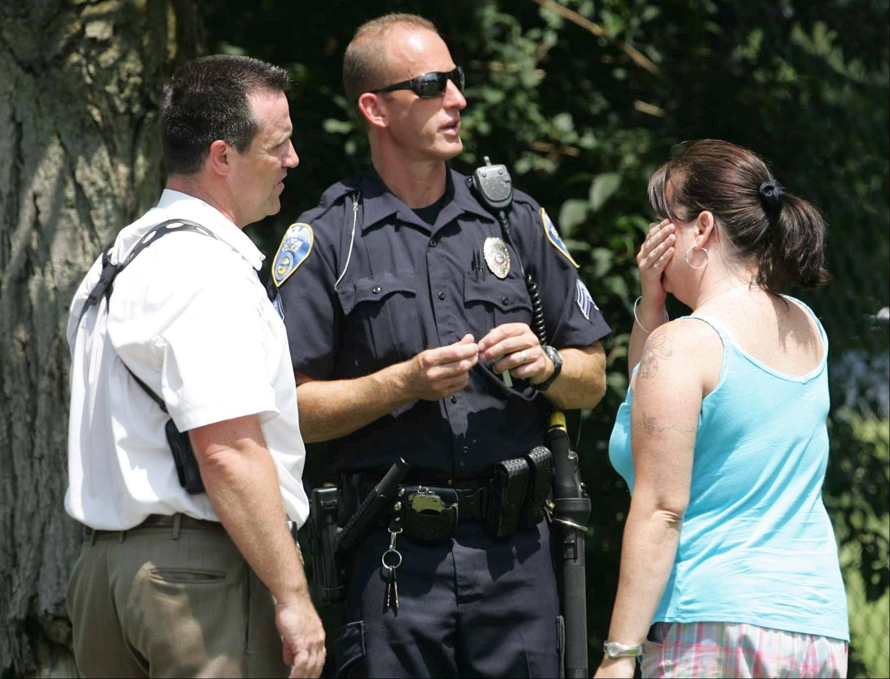 Members of the Akron Police Department talk to an unidentified woman who claimed to be a relative at the scene of a multiple fatal shooting Sunday in Copley Township, Ohio.