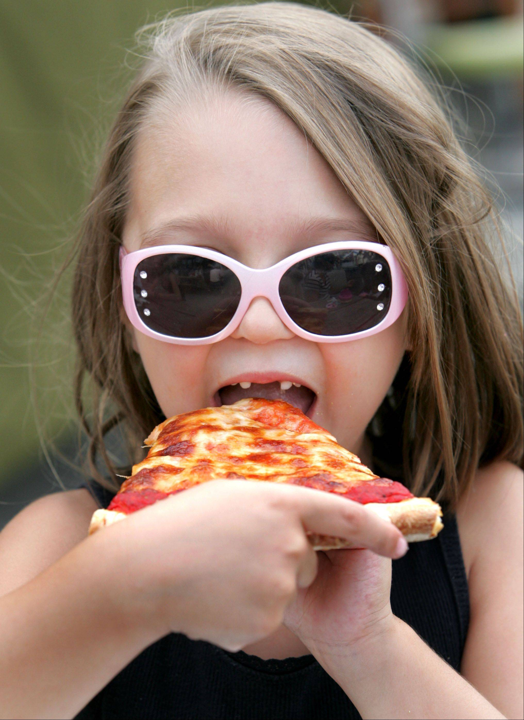 Gracie Caputo, 5, doesn't let a lack of front teeth stop her from taking a bite of pizza during opening day of the Taste of Roselle on Friday.
