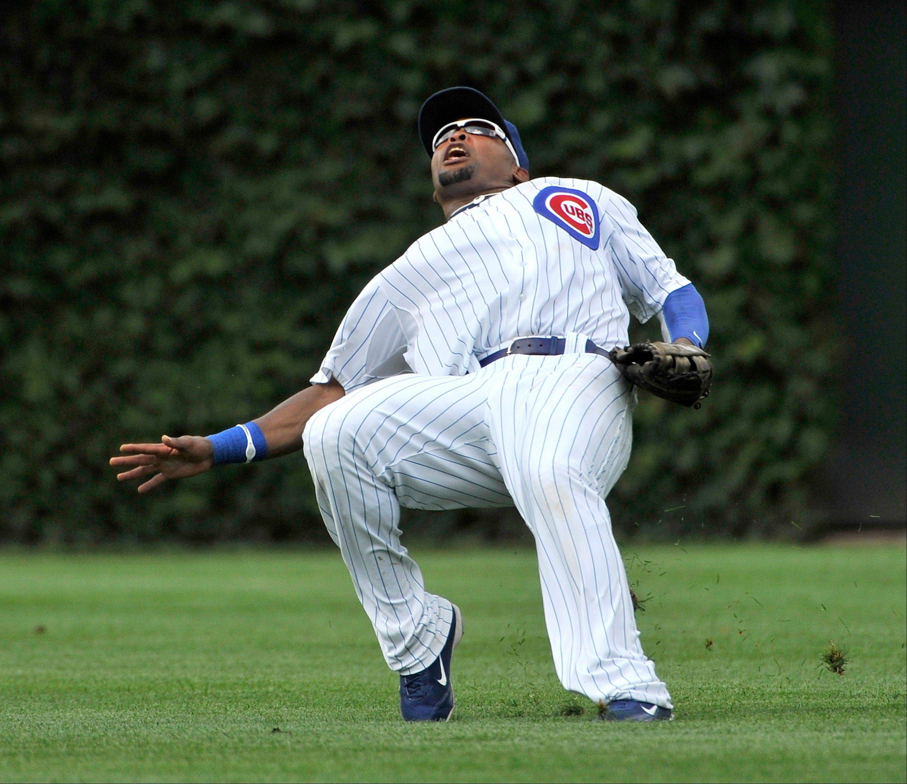 Cubs center fielder Marlon Byrd slips on the wet outfield grass while chasing a Joey Votto pop fly leading off the eighth inning Sunday. The ball fell in for a double and the Reds went on to score the go-ahead run in the inning.