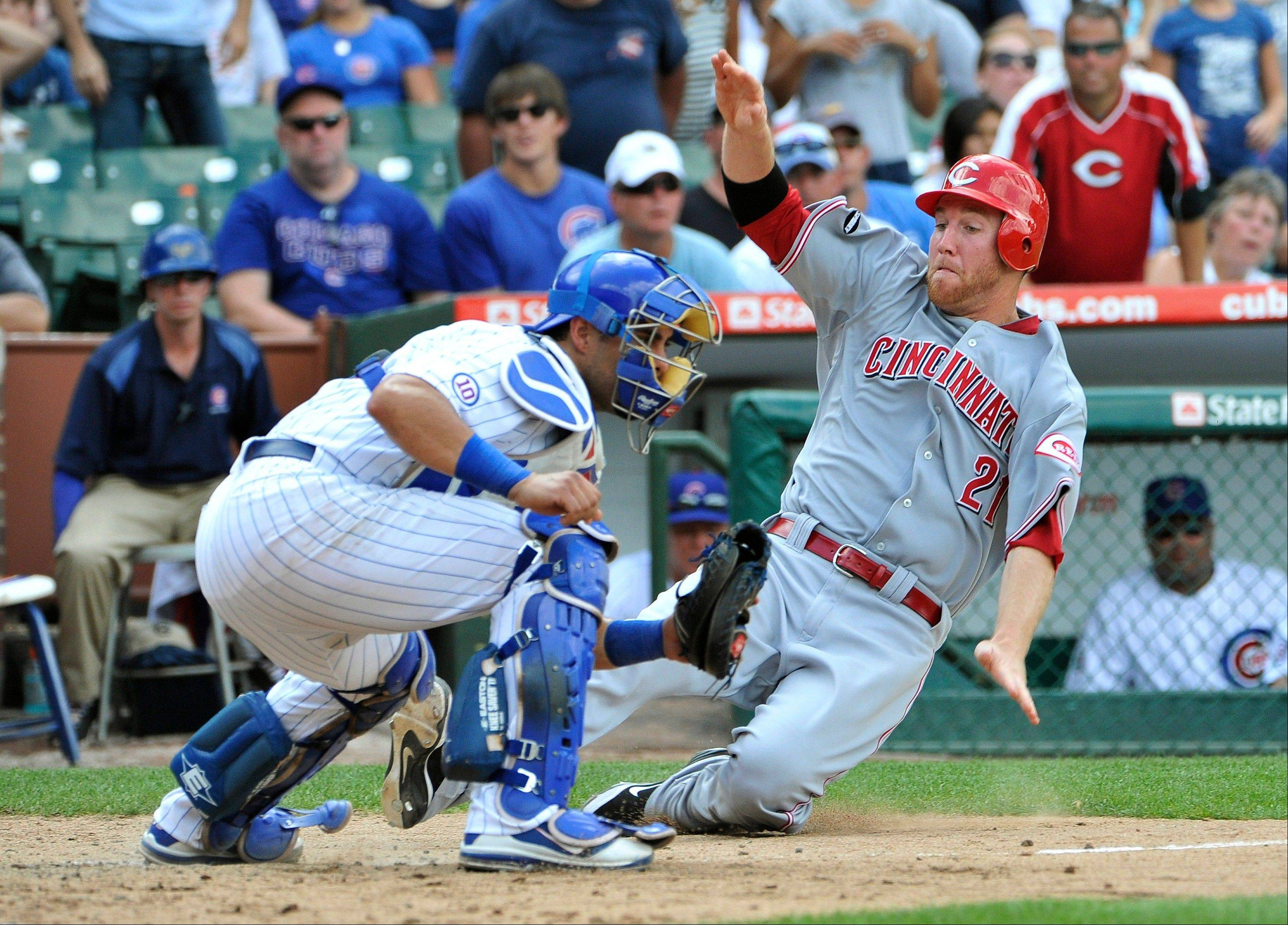 The Reds' Todd Frazier scores past Geovany Soto on a hit by Ryan Hanigan during the eighth inning Sunday in Chicago.