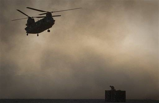 A U.S. Marine tries to take cover, perched on a container, trying to shelter from the dust as a Chinook helicopter like the one shot down this weekend attempts a rescue.