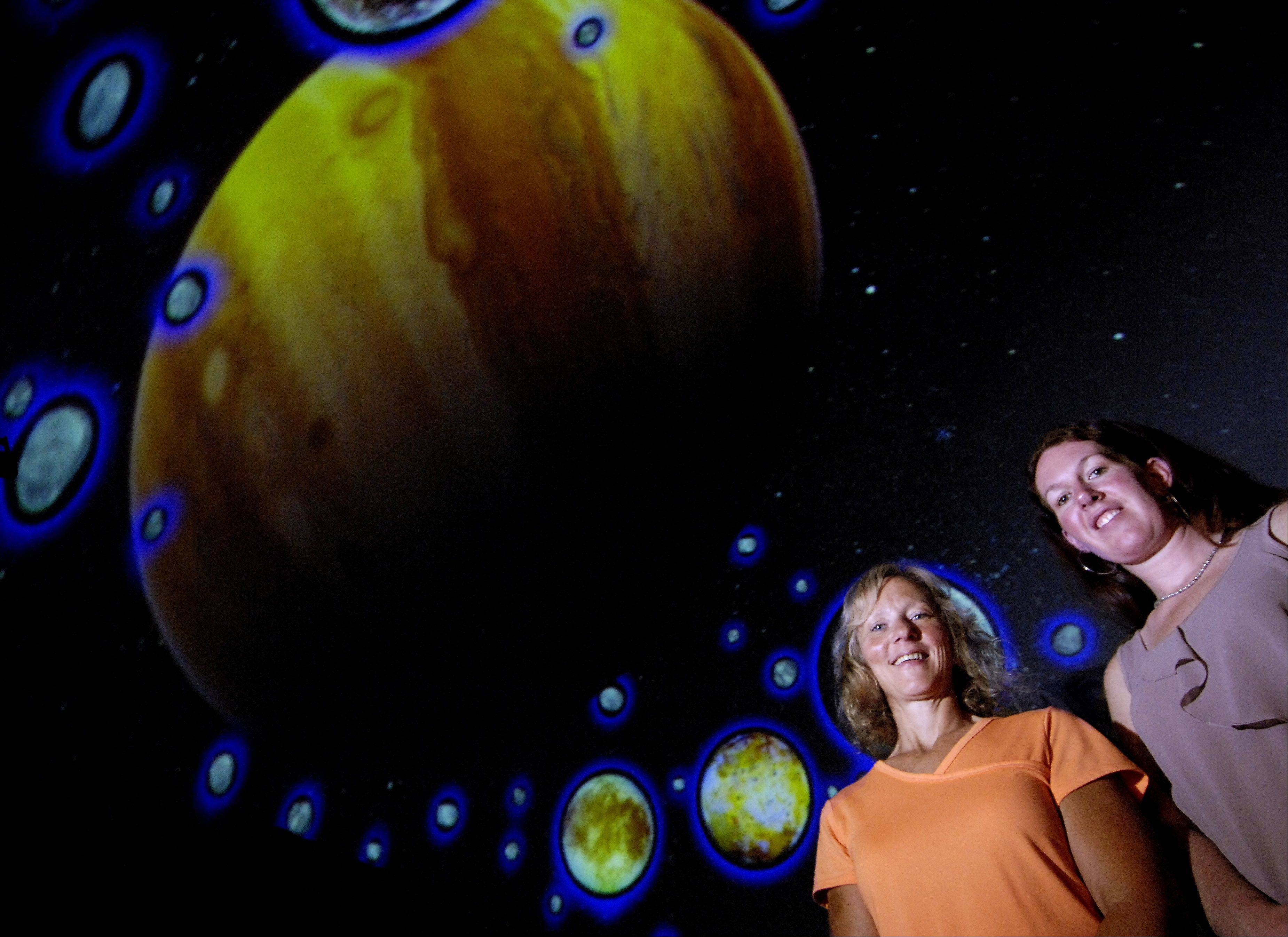 Peggy Hernandez, left, and Jennifer McDonnell stand in the Elgin Area School District U-46 Planetarium in front of a scene using its new full-dome projector. Hernandez is a teacher and director of the planetarium. McDonnell is coordinator of Math, Science, Planetarium & Instructional Technology for U-46.