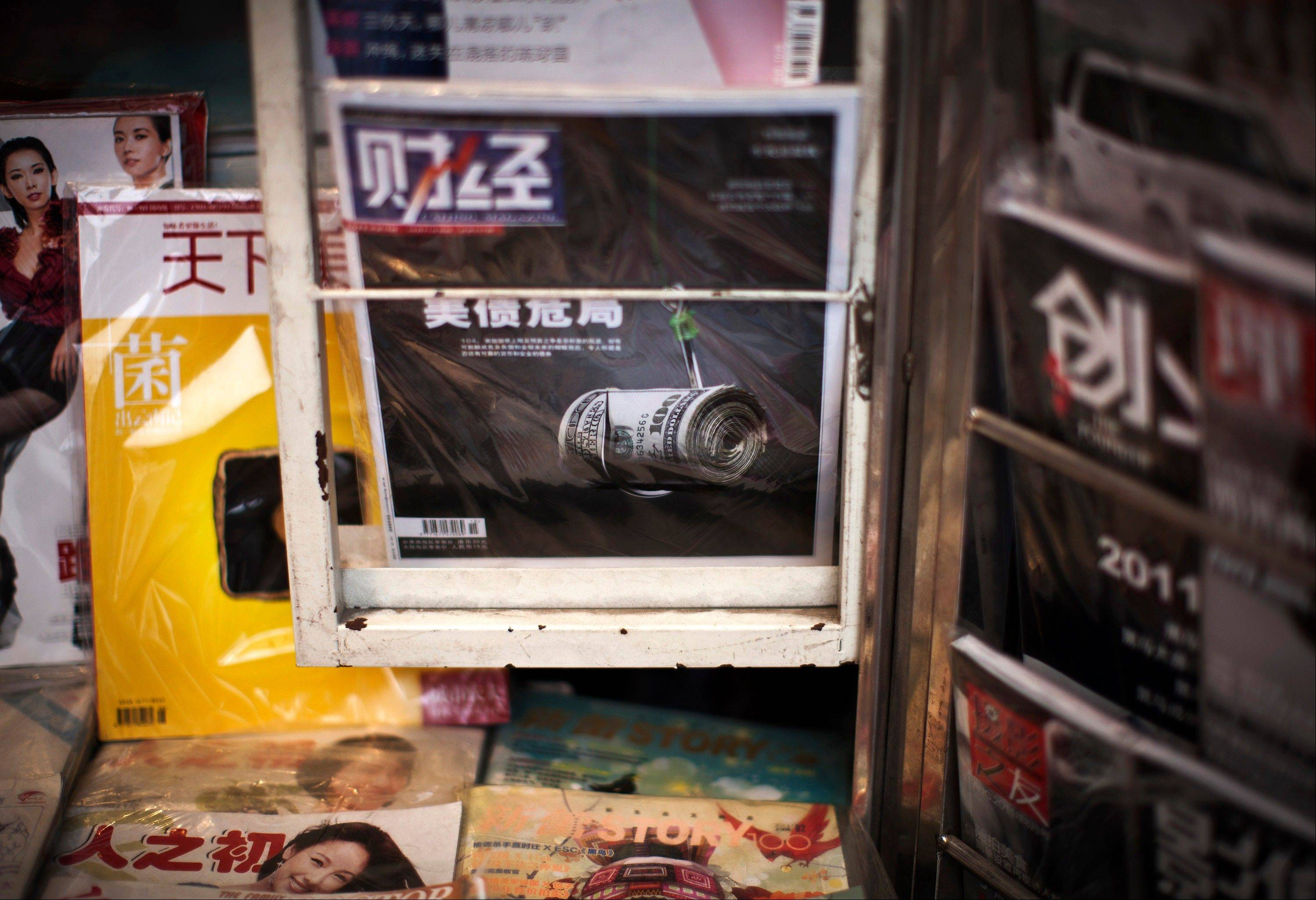 A copy of Chinese financial magazine featuring the U.S. debt crisis, center, is on sale at a newsstand in Beijing Monday. China, the largest foreign holder of U.S. debt, demanded Saturday America tighten its belt and confront its �addiction to debts.�