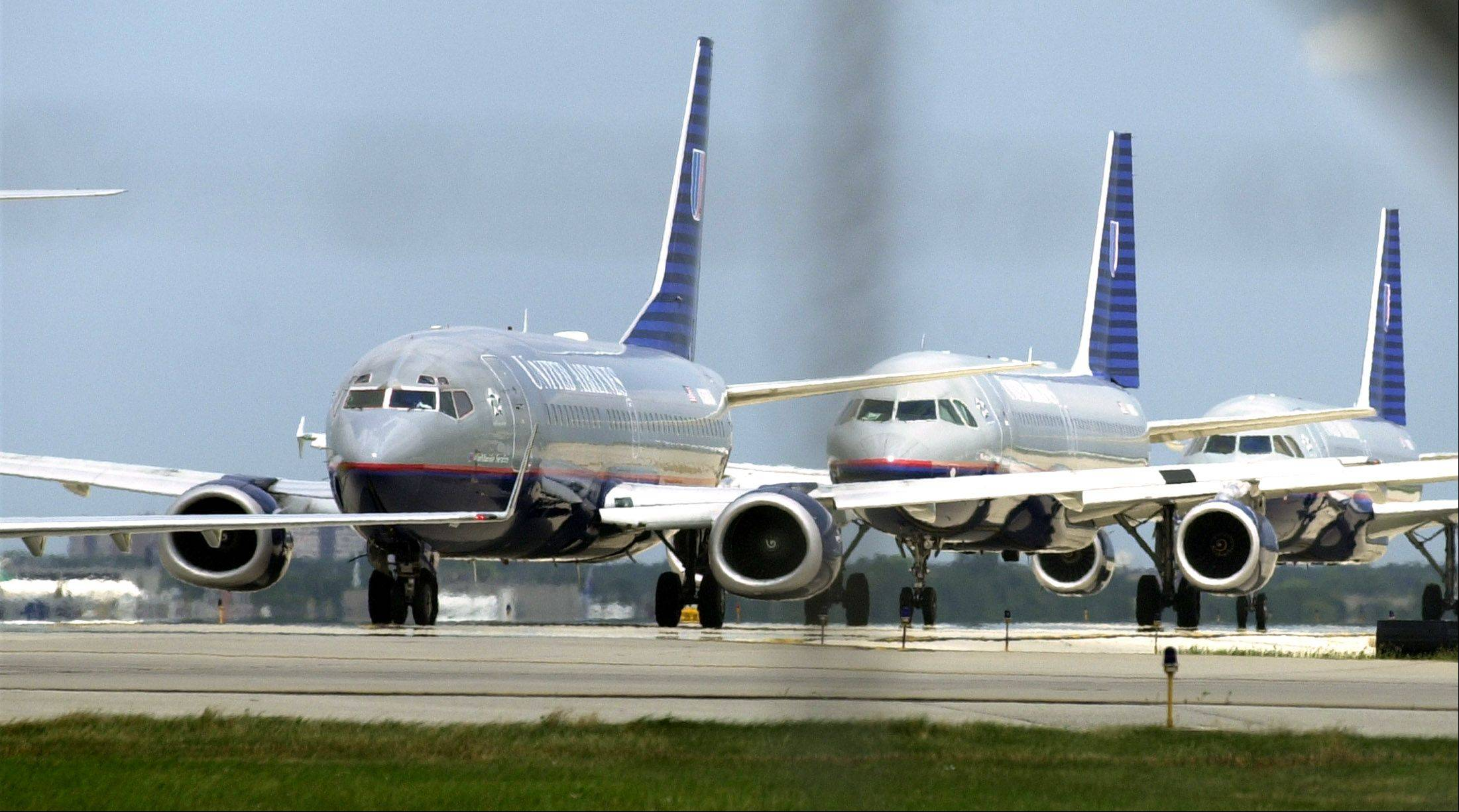 United Airlines planes line up for takeoff at O�Hare International Airport. U.S. airlines have started rolling back last month�s fare increases.