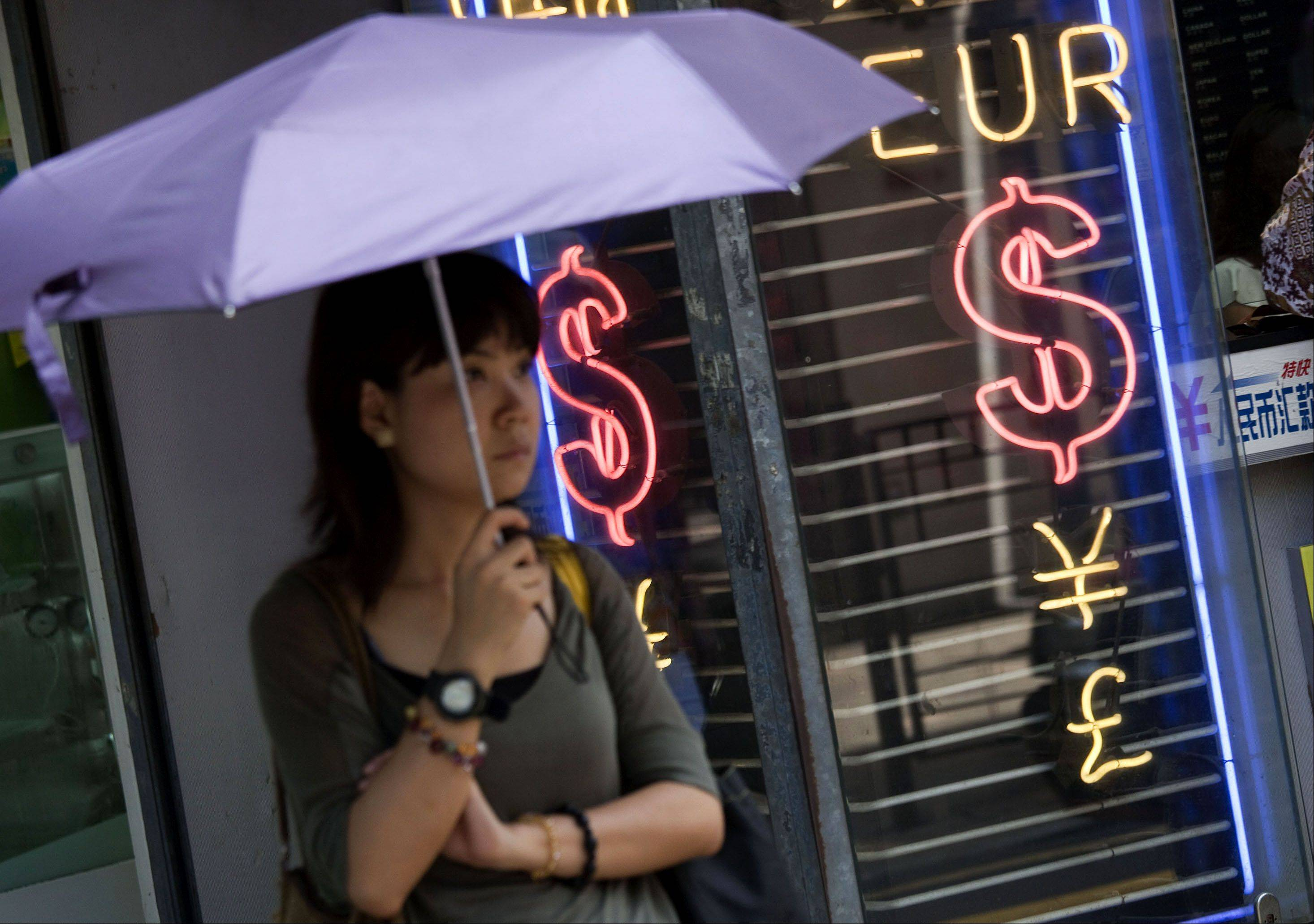 "A woman shelters next to a currency exchange bureau in Hong Kong, China, on Monday, Aug. 8, 2011. The Hong Kong Monetary Authority, with foreign currency assets worth $288 billion as of June 30, said U.S. bonds and the dollar are still ""safe""."