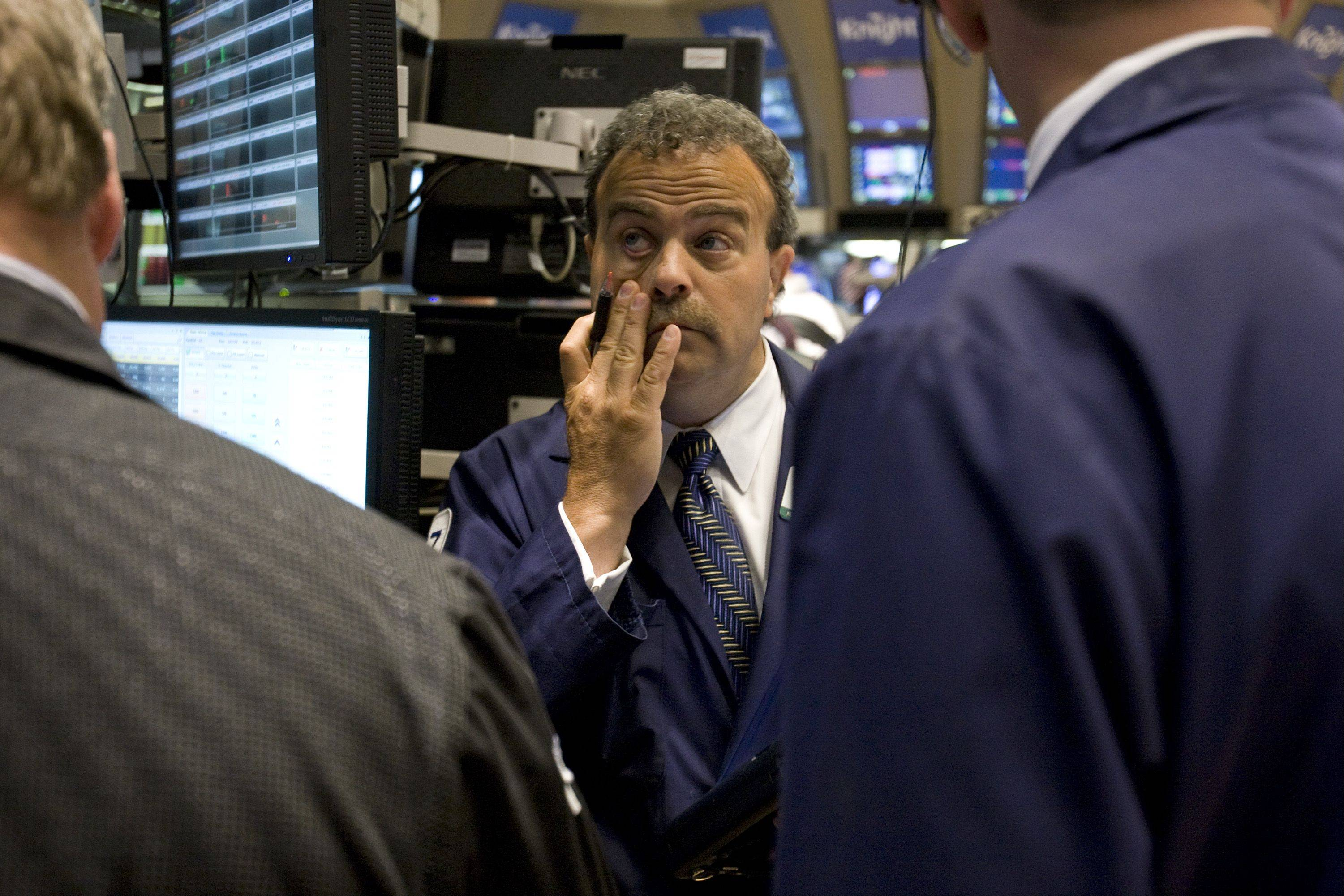 Traders work on the floor of the New York Stock Exchange (NYSE) in New York, U.S., on Monday, Aug. 8, 2011. U.S. stock futures retreated, following the biggest weekly drop in the Standard & Poor's 500 Index since 2008, amid concern that a downgrade of the nation's credit rating by S&P may worsen an economic slowdown.