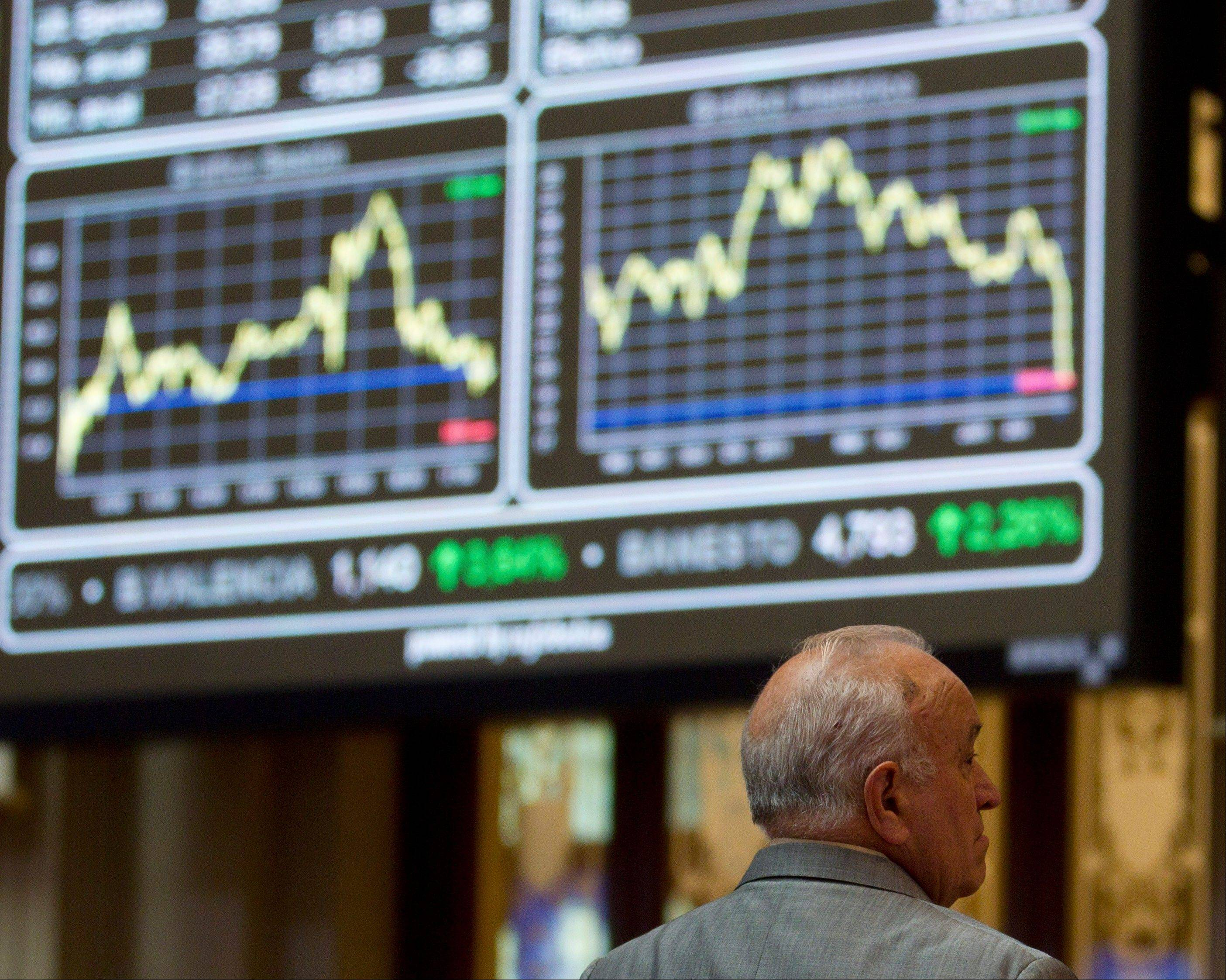 A broker looks on in front of the main screen at the Stock Exchange in Madrid Monday Aug. 8, 2011. The borrowing costs of both Spain and Italy dropped sharply in early trading Monday after the European Central Bank signaled it would intervene in the markets to keep the two countries' bond prices supported. (AP Photo/Paul White)