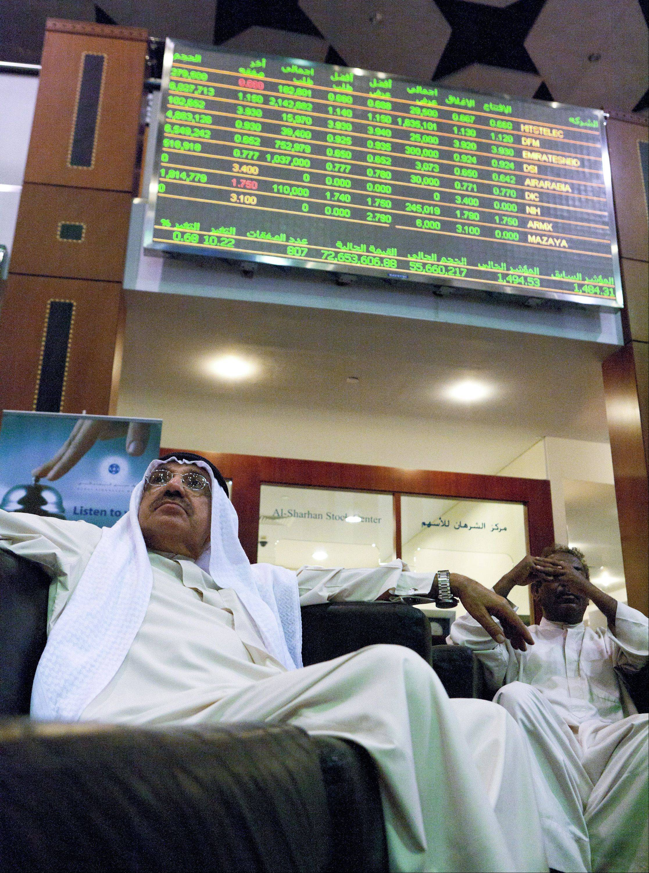 Visitors watch financial data on screens inside the Dubai Financial Market in Dubai, United Arab Emirates, on Monday, Aug. 8, 2011. Dubai's stock index retreated to the lowest since March as global financial markets slumped amid concern that Standard & Poor's downgrading of the U.S.'s credit rating may stall the global economic recovery.