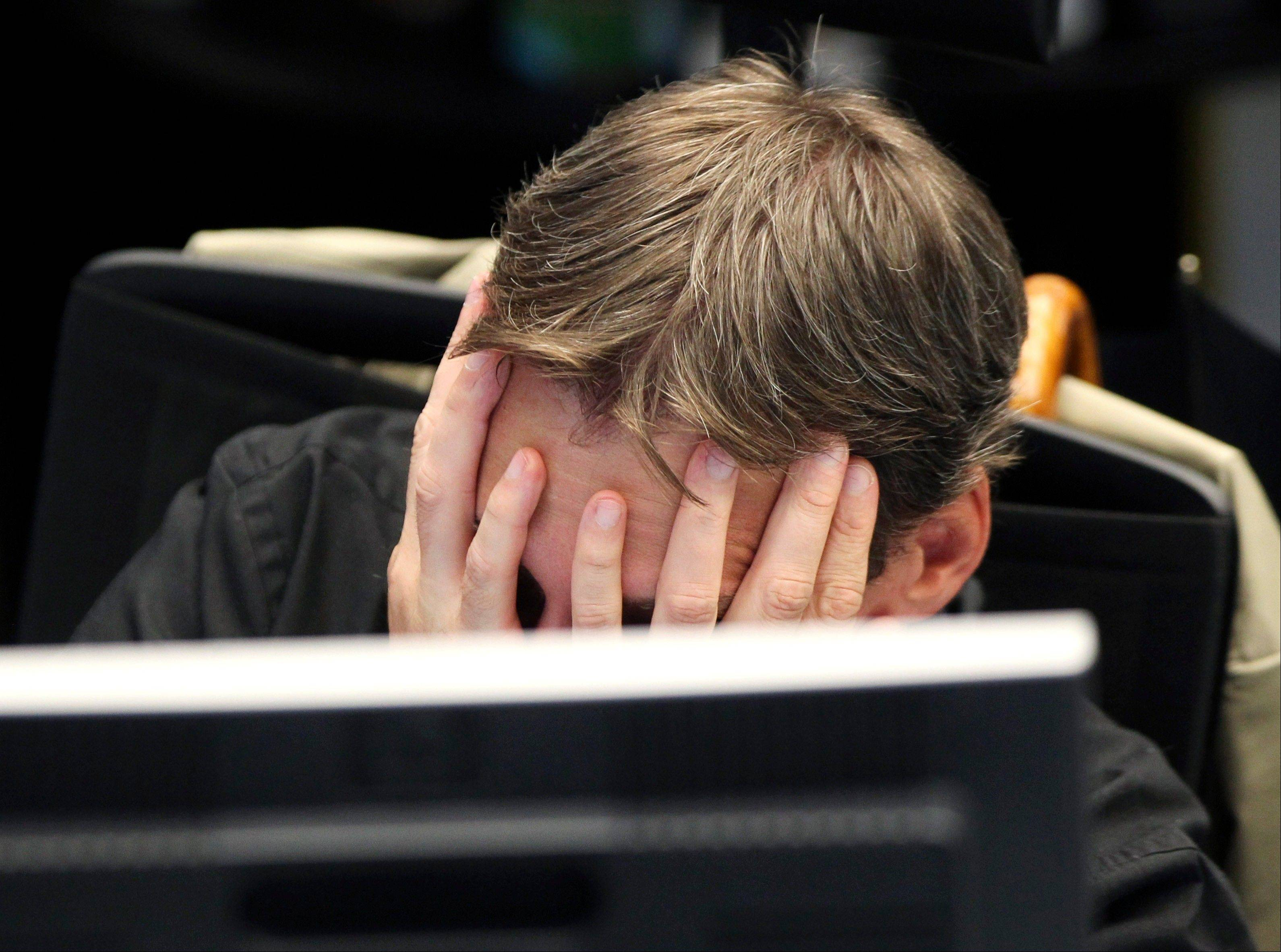 A broker covers his face behind his screen at the stock market in Frankfurt, Germany, Monday, Aug. 8, 2011, where the stock index went down after the opening of the stock market.