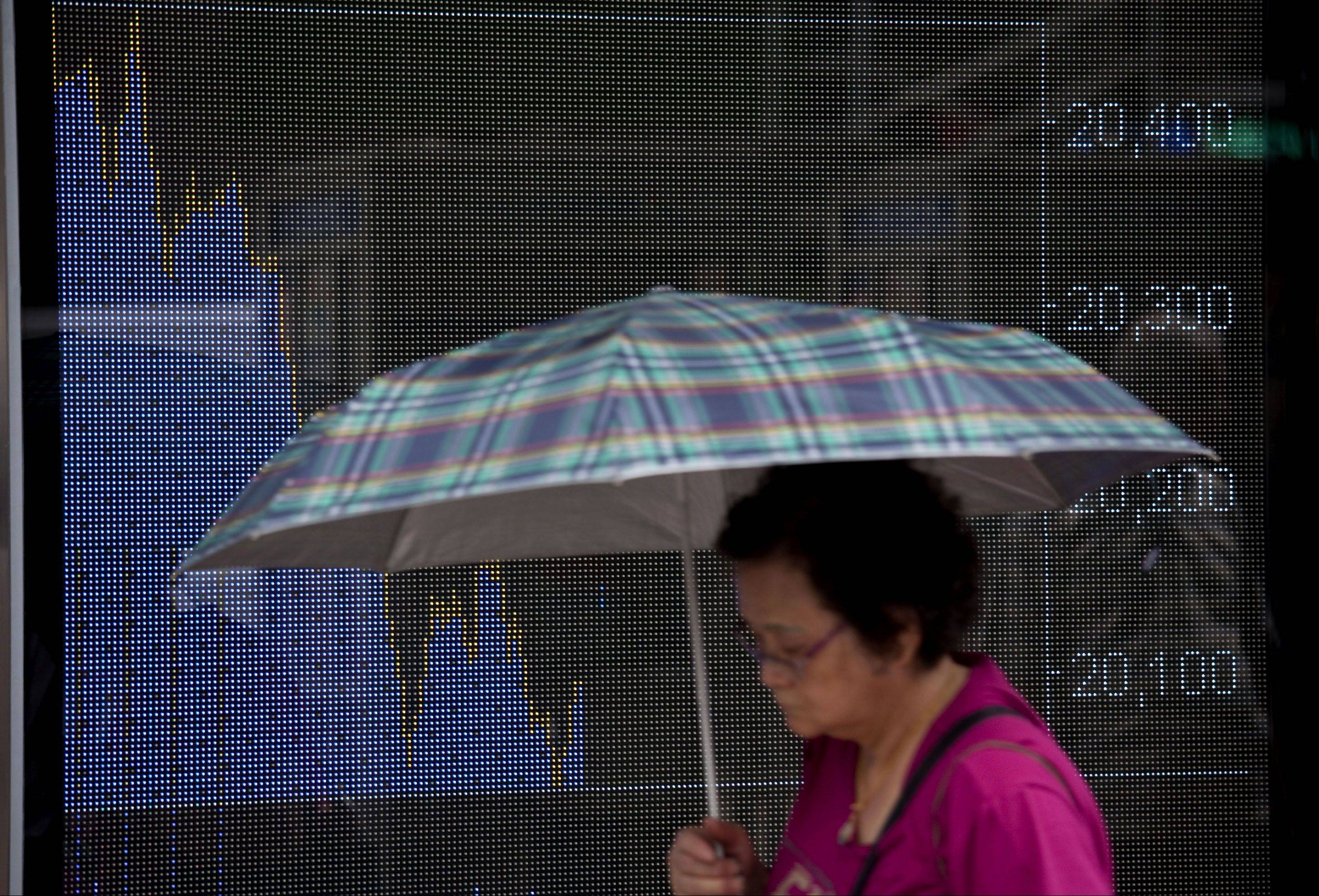 A woman walks past an electronic billboard displaying the Hang Seng Index intraday chart in Hong Kong, China, on Monday, Aug. 8, 2011. Hong Kong stocks dropped, with the benchmark Hang Seng Index set for its biggest two-day slide since October 2008, after Standard & Poor's cut the U.S. credit rating, raising concern global economic growth will slow.