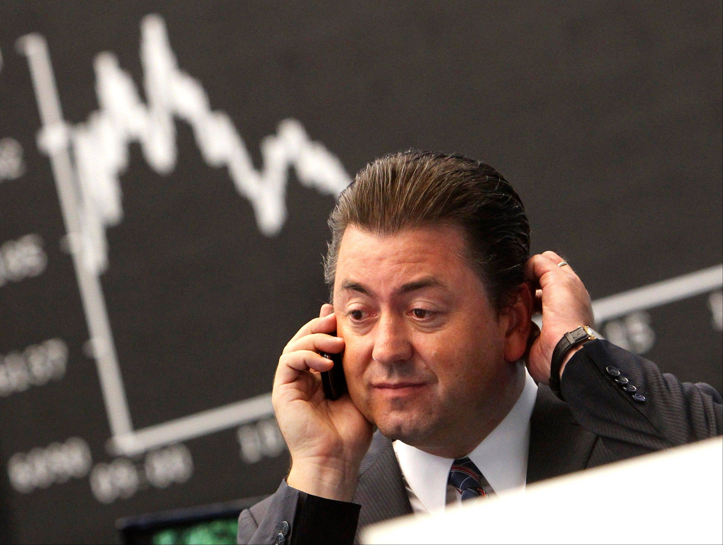 Robert Halver, chief analyst of a German private bank makes a phone call under the curve of the German stock index DAX at the stock market in Frankfurt, Germany, Monday, Aug. 8, 2011, where the stock index went down after the opening of the stock market.