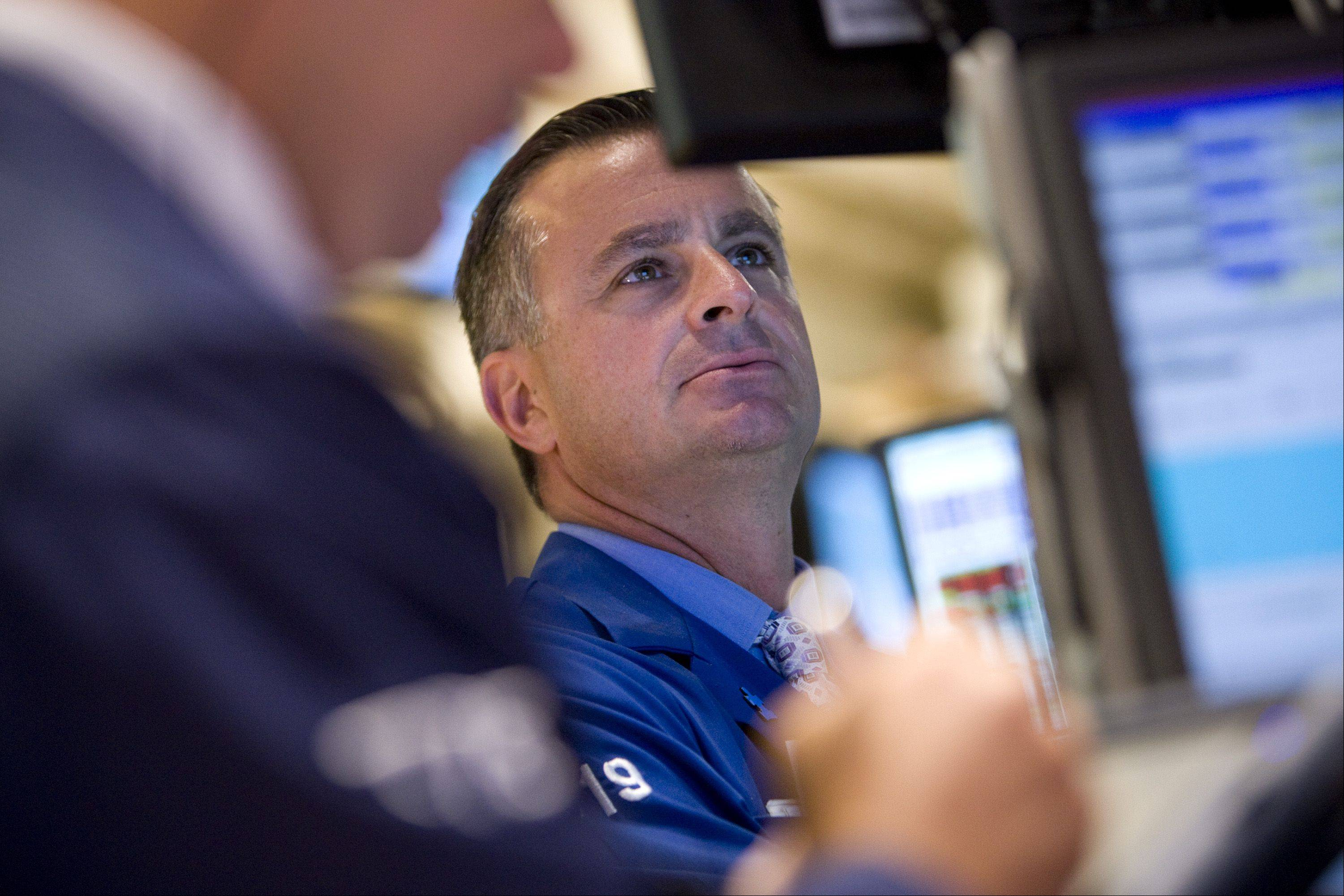 A trader works on the floor of the New York Stock Exchange (NYSE) in New York, U.S., on Monday, Aug. 8, 2011. U.S. stock futures retreated, following the biggest weekly drop in the Standard & Poor's 500 Index since 2008, amid concern that a downgrade of the nation's credit rating by S&P may worsen an economic slowdown.