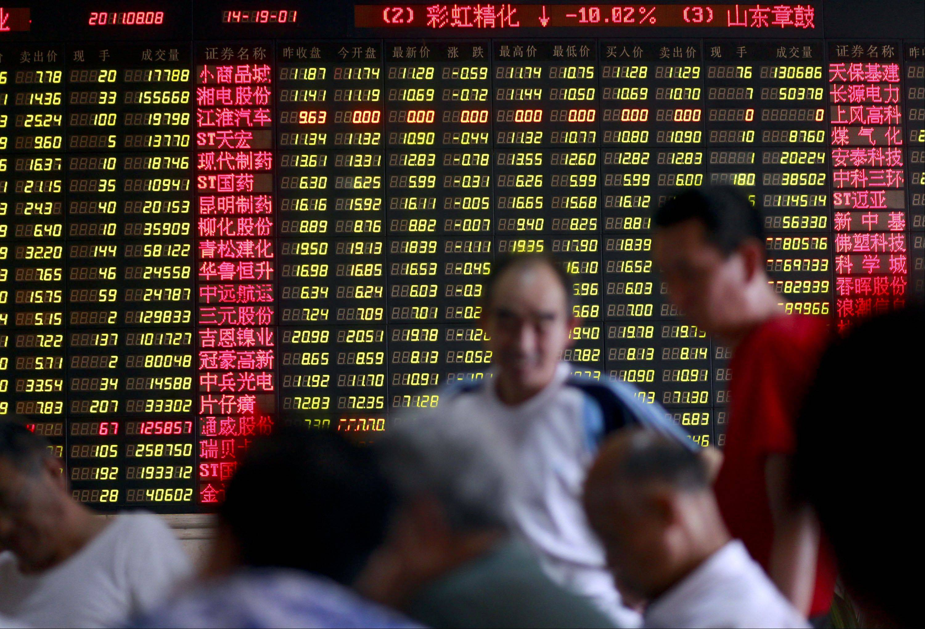 Investors monitor prices and make trades at a securities exchange house in Shanghai, China, on Monday, Aug. 8, 2011. China's stocks fell, dragging the benchmark index down 20 percent from a November high, as the loss of America's top credit rating fueled concern global economic growth will slow.