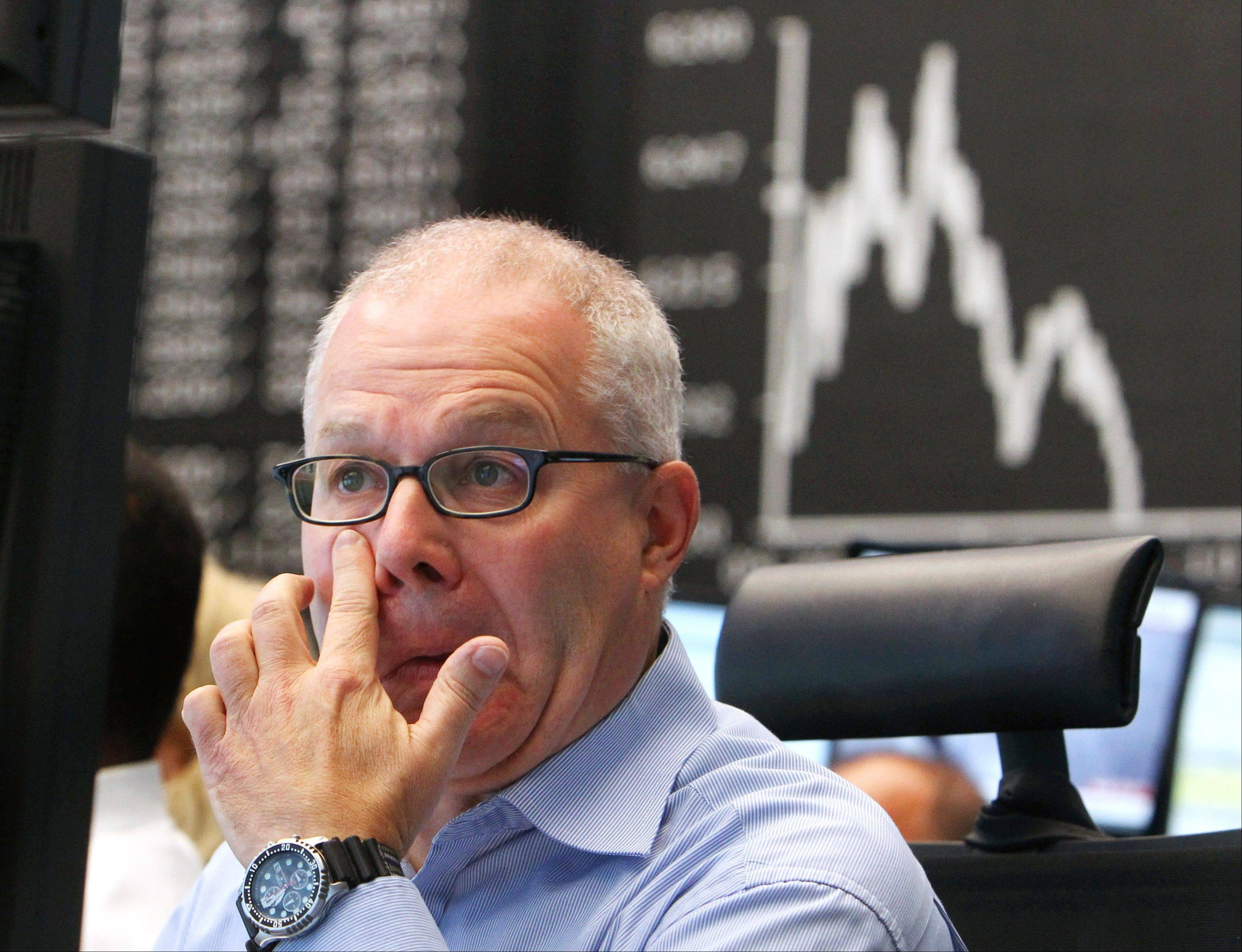 A broker watches his screens under the curve of the German stock index DAX at the stock market in Frankfurt, Germany, Monday, Aug. 8, 2011, where the stock index went down after the opening of the stock market.