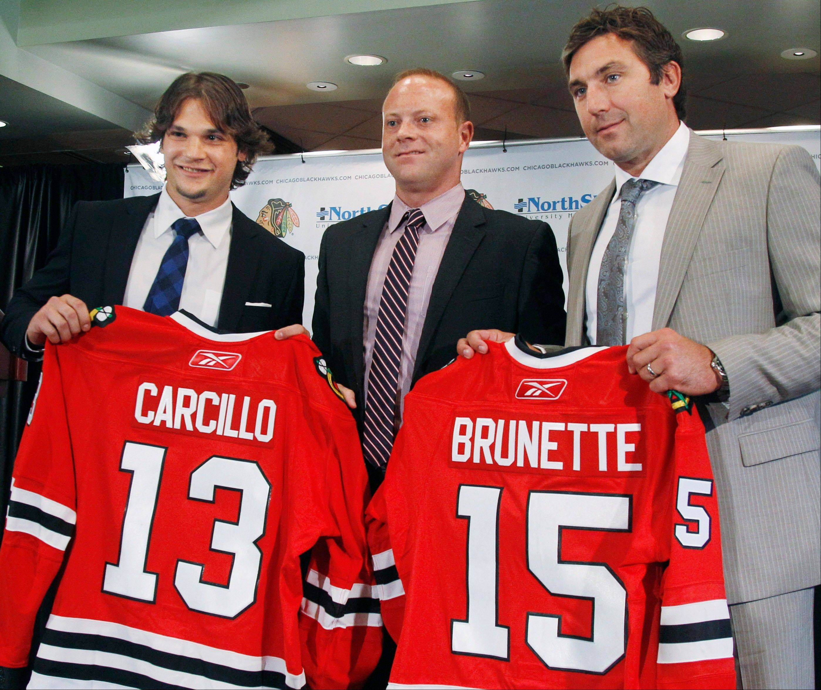 New Chicago Blackhawks free agent signees Daniel Carcillo and Andrew Brunette pose with general manager Stan Bowman after being introduced at a news conference Monday.