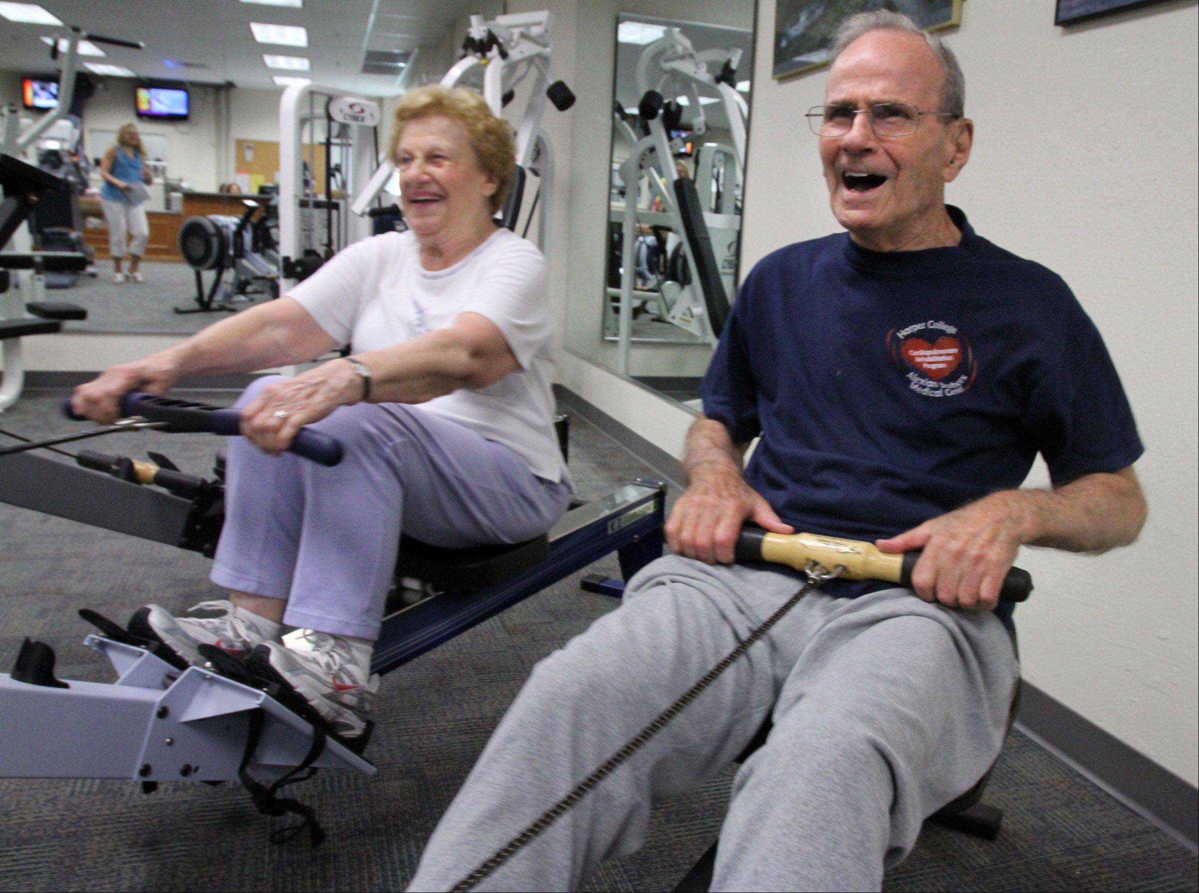 Sam Greco, 90, and Bess Greco, 85, of Palatine, exercise on the rowing machine at the Fitness Center at Harper College.