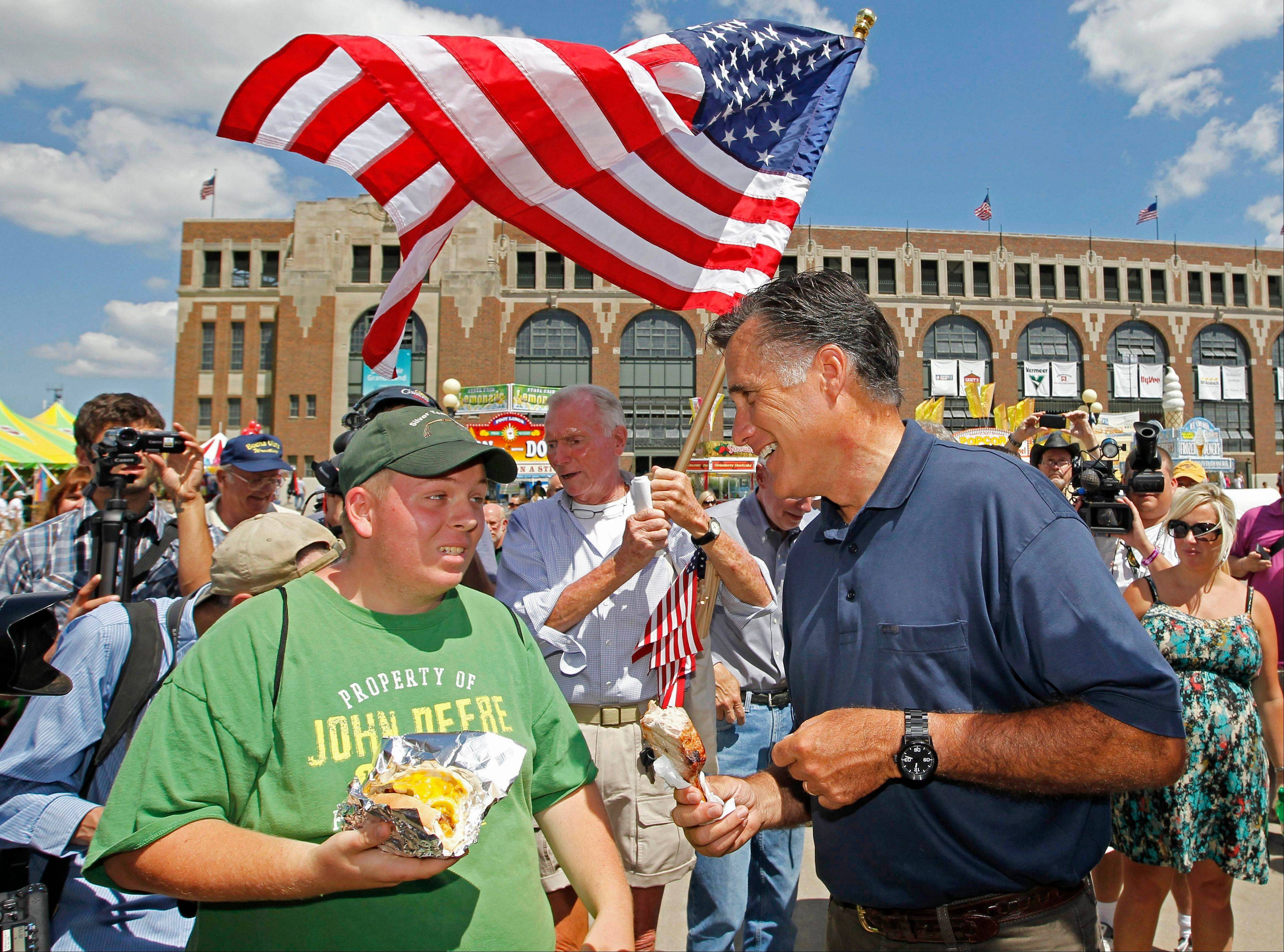 Republican presidential candidate former Massachusetts Gov. Mitt Romney, holding a pork chop on a stick, talks to visitors as he campaigns at the Iowa State Fair in Des Moines on Thursday.