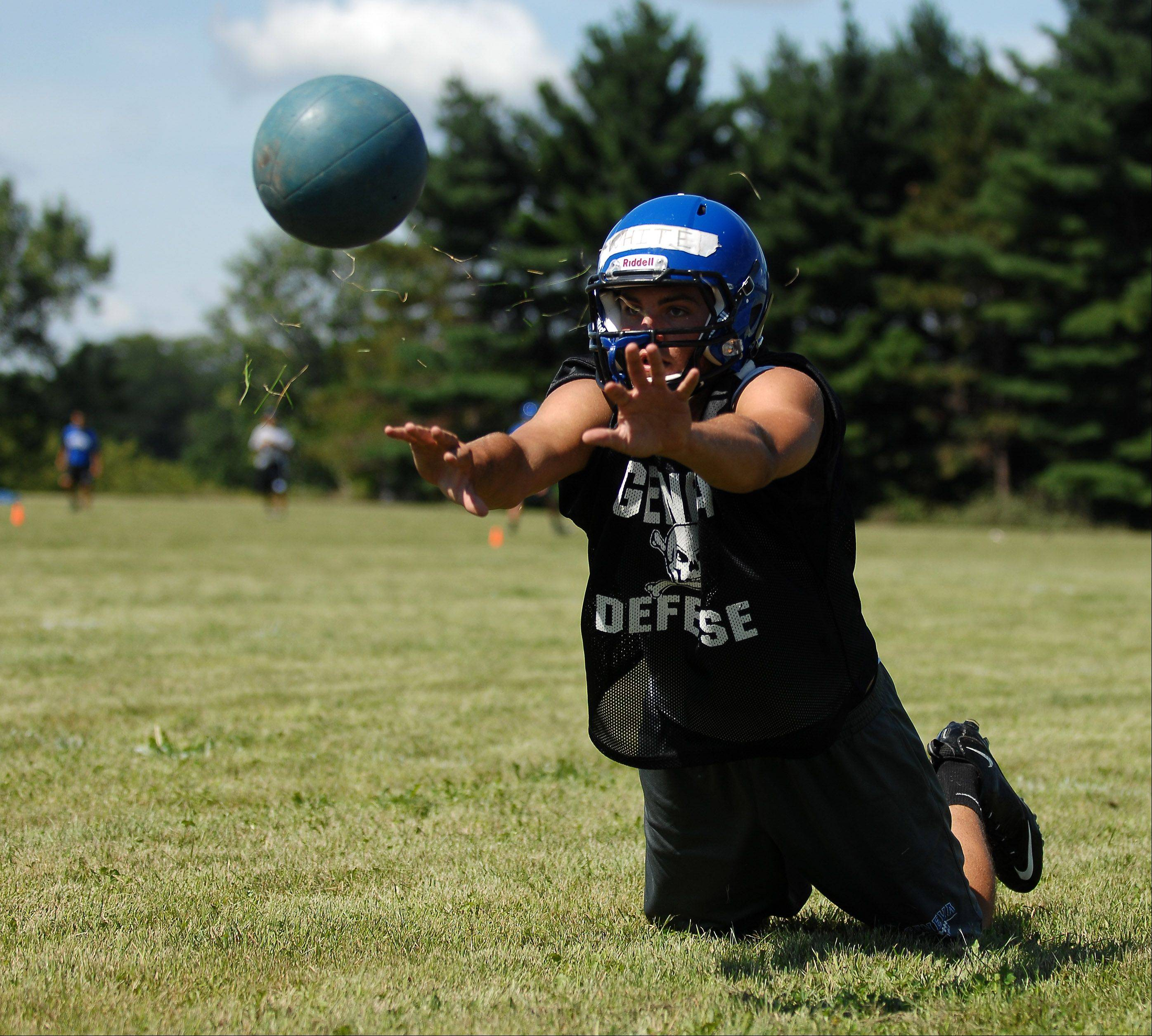 Drew White lunges and throws a medicine ball during Wednesday's first day of football practice for Geneva High School at the former Broadview Academy site in La Fox.