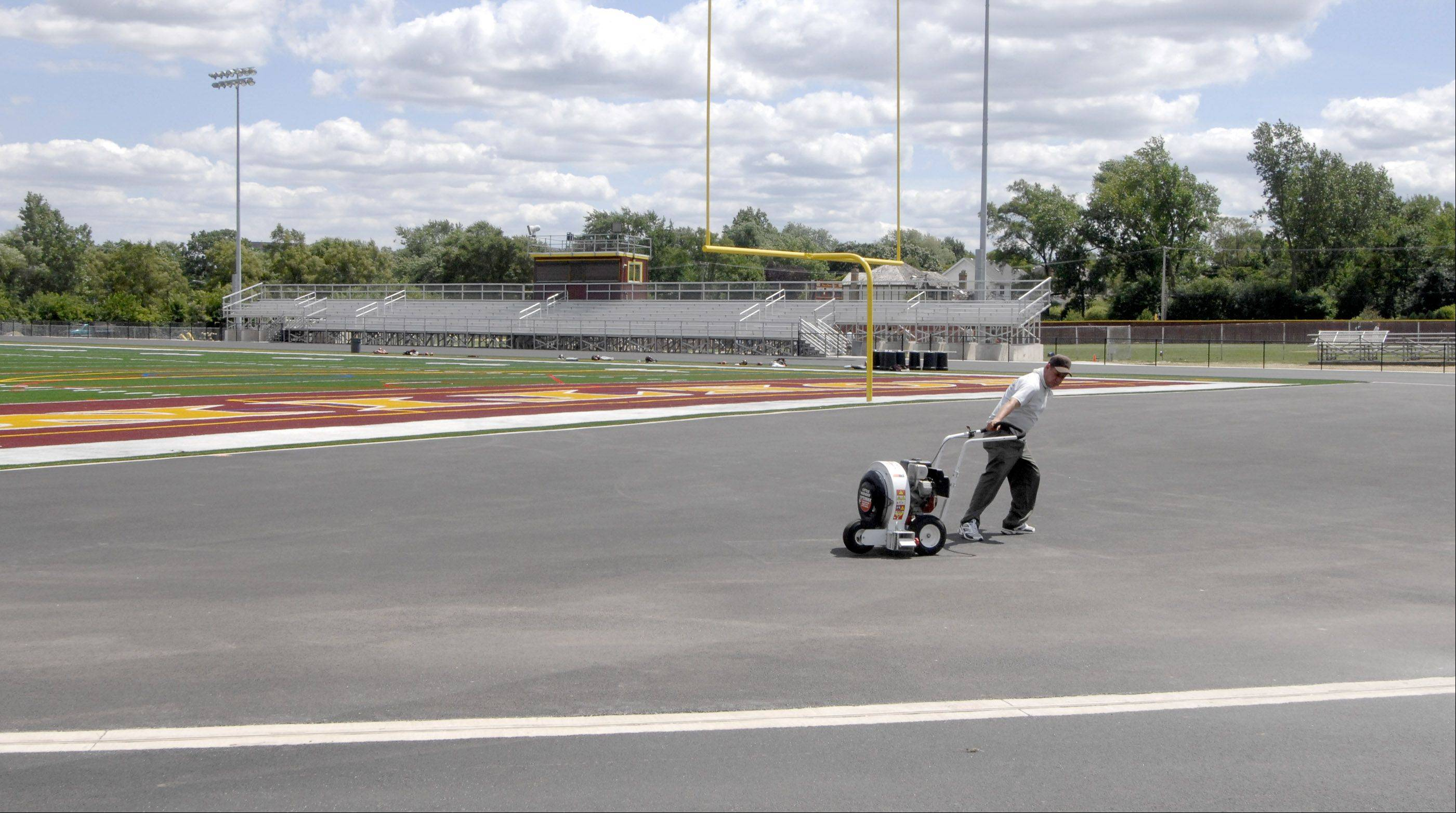 Workers are preparing the track at Lombard's Montini Catholic High School to be coated with a new rubber surface. On Wednesday all of the dust and dirt was removed but the actual coating will begin today.