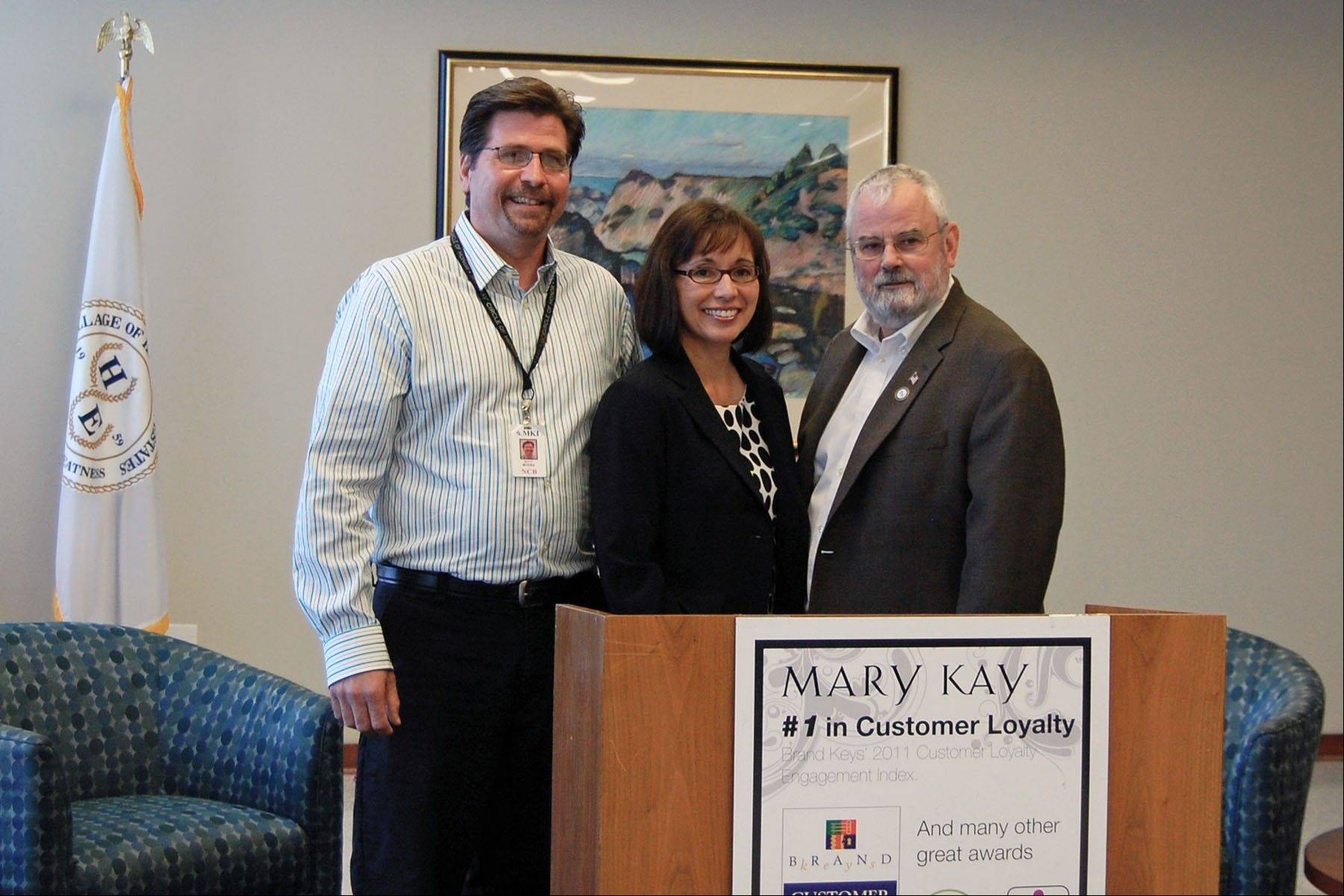 Hoffman Estates Mayor William D. McLeod, right, presents a certificate of recognition to representatives from Mary Kay, Inc., which is headquartered in the village's Prairie Stone Business Park, for their focus on green business practices.