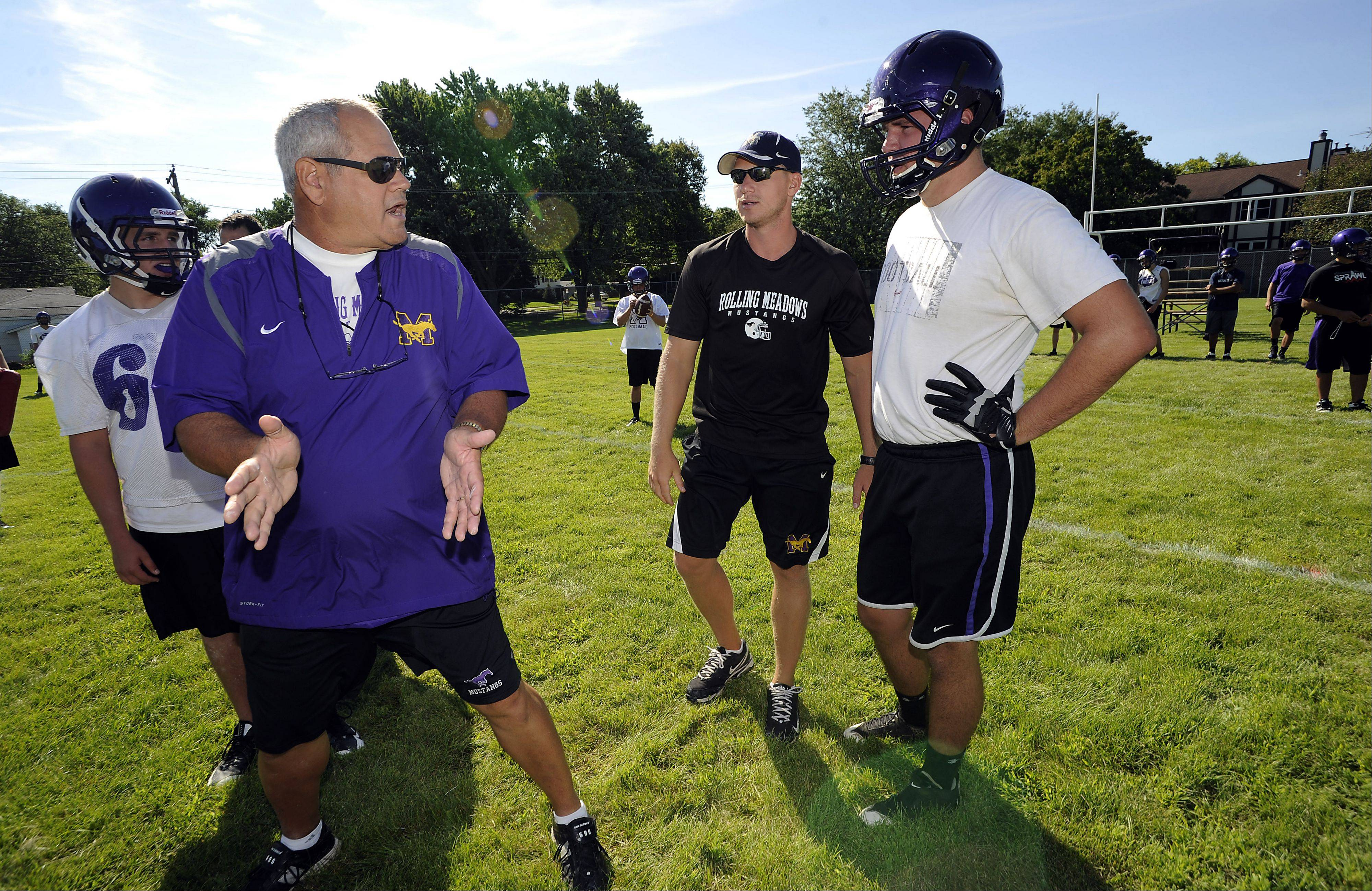 Rolling Meadows offensive line coach Jim Rucks, left, and new head coach Matt Mishler work with Nick Leidecker during Wednesday's practice. Mishler played quarterback for Rucks at Hoffman Estates.