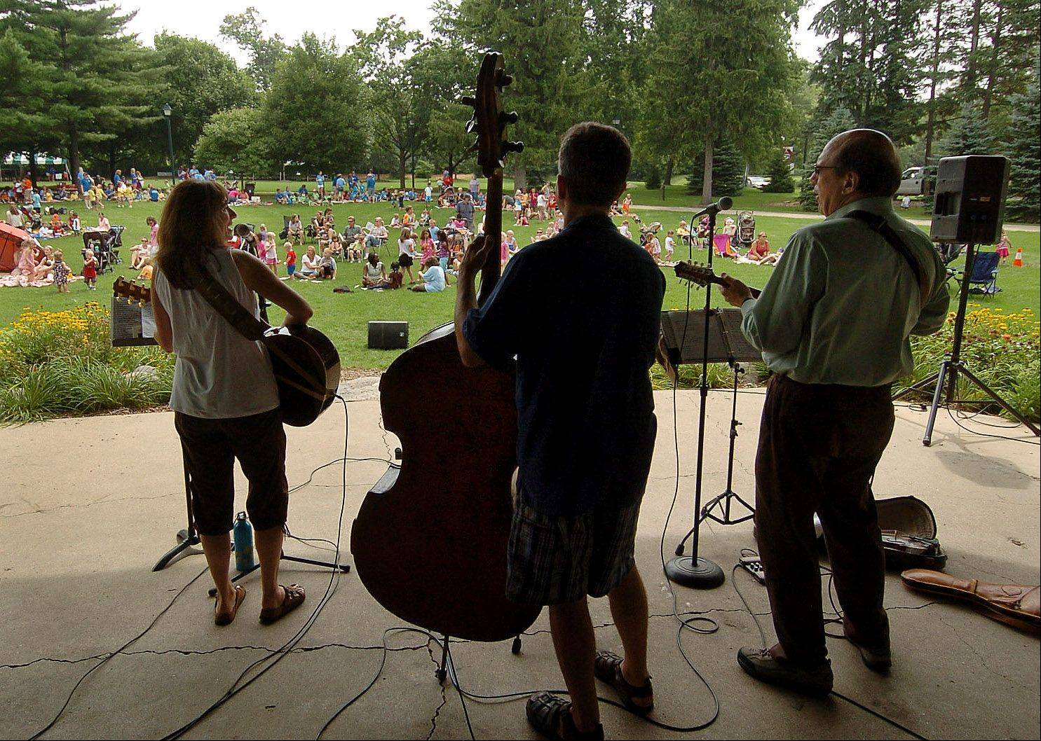 Children's performer Karen Jordan, left, along with Jim Cox, center, and Don Stiernberg perform at Viking Park for the final Children's Concerts show sponsored by the Gurnee Park District.