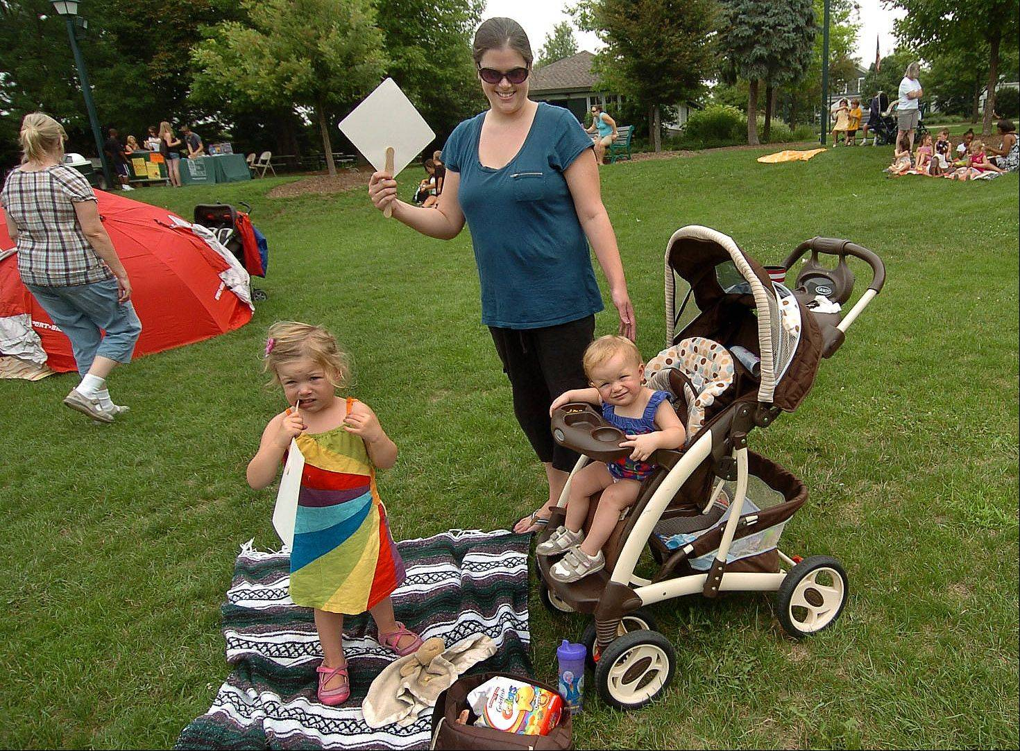 Melissa Smith of Antioch fans her kids, Lilly, left, and Elsie, from the heat while watching Karen Jordan perform at Viking Park for the final Children's Concerts show sponsored by the Gurnee Park District.