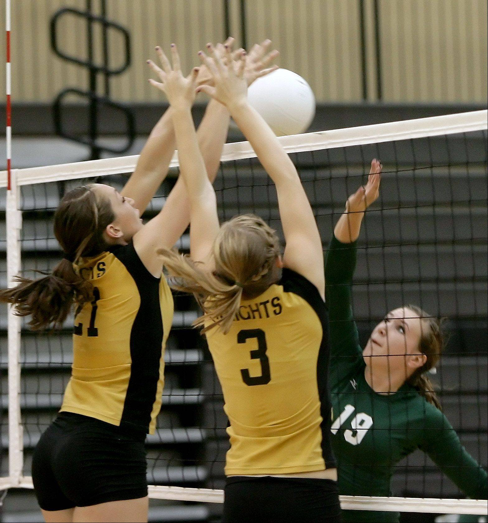 Grayslake North players Felicia Stancil, left, and Katie McGrath set up a block opposite Grayslake Central's Hannah Smith last fall.