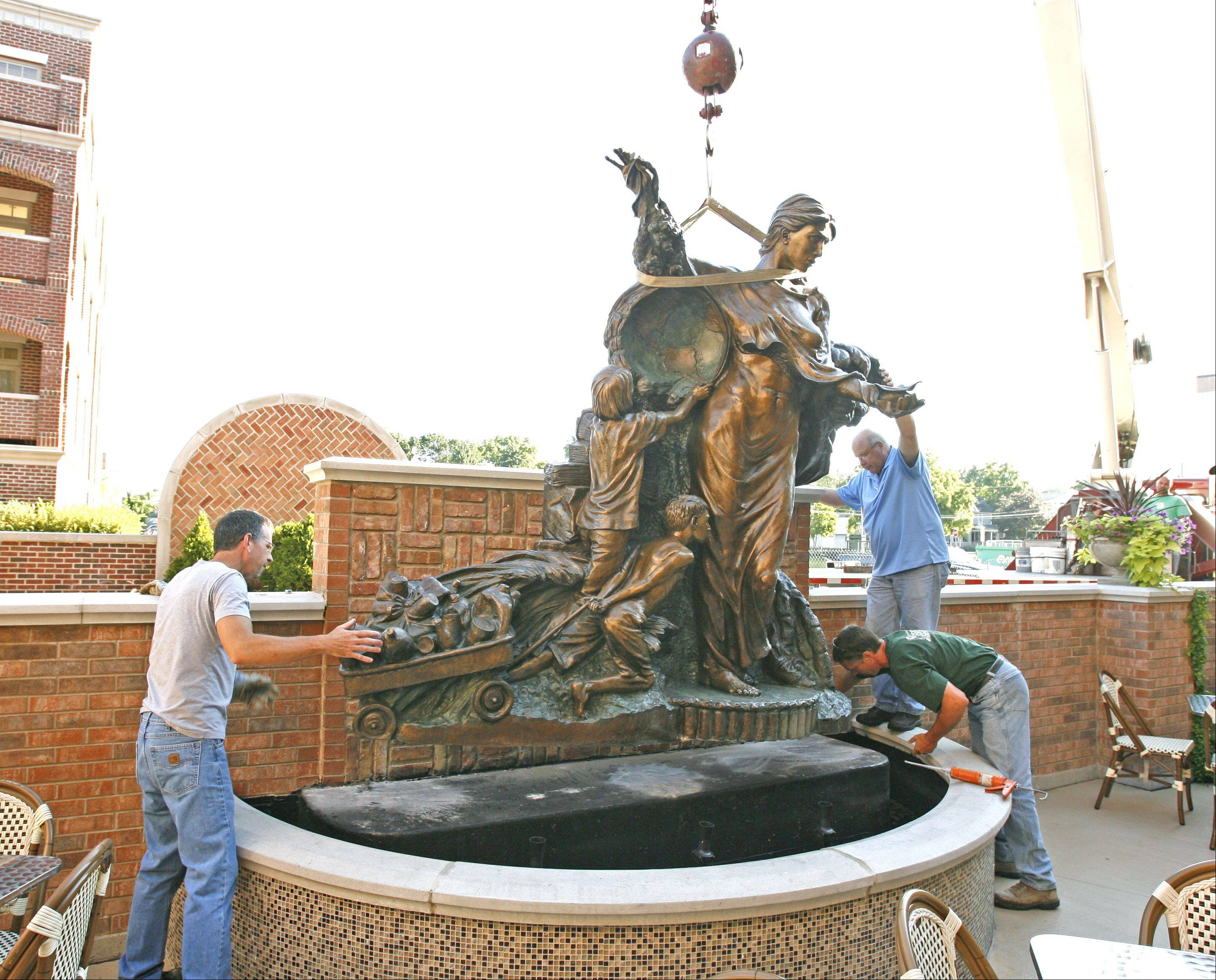 The 2,400-pound Symbiotic Sojourn sculpture was moved as part of the $200,000 renovation of the patio at Main Street Promenade in downtown Naperville. Sculptor Jeff Adams, left, cleaned and sealed the piece before its return Thursday to Naperville.