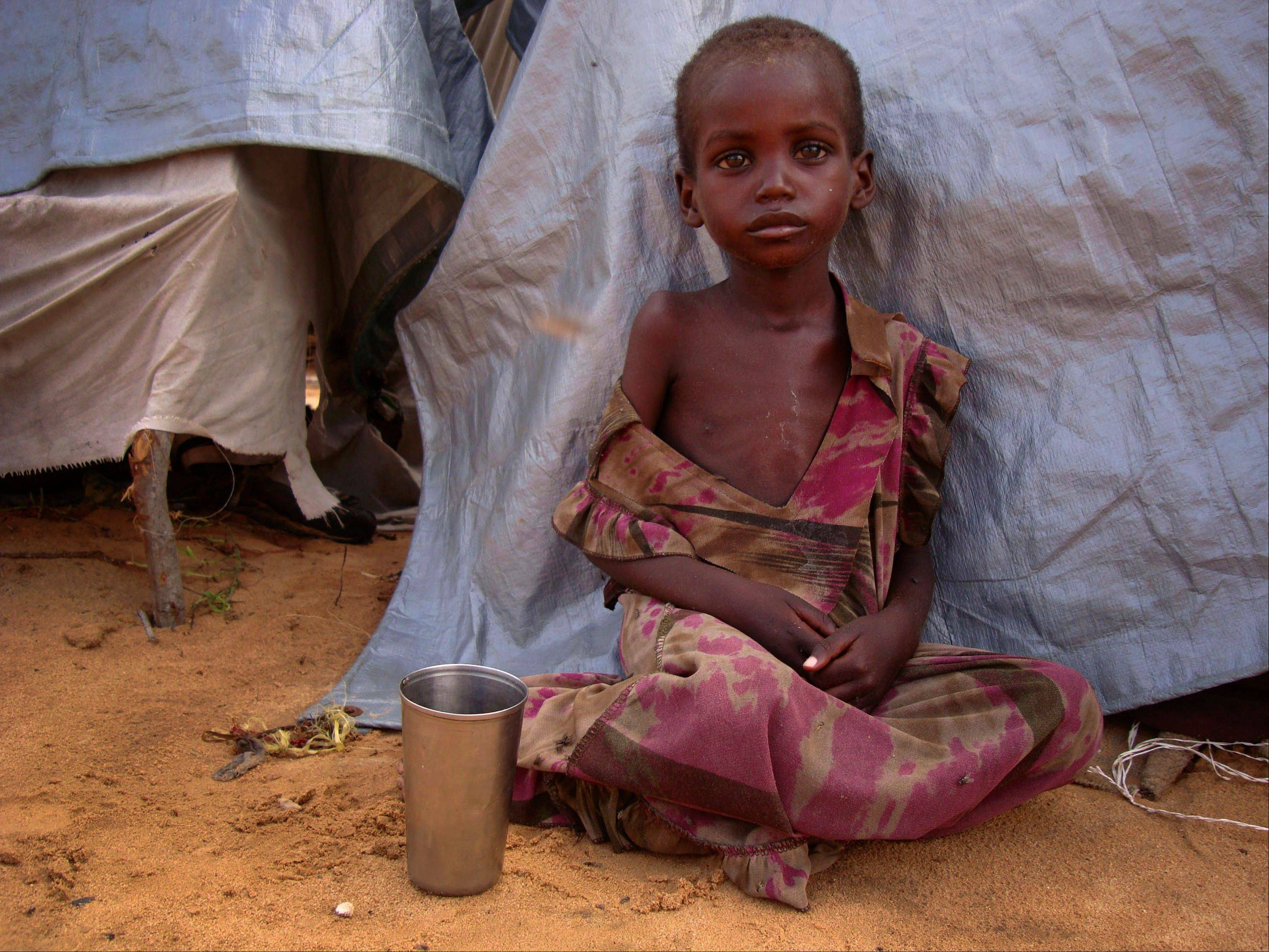 A girl from southern Somalia sits outside a makeshift shelter at a refugee camp in Mogadishu, Somalia, Tuesday, Aug 9, 2011. The number of people fleeing famine-hit areas of Somalia is likely to rise dramatically and could overwhelm international aid efforts in the Horn of Africa, a U.N. aid official said Tuesday. (AP Photo/Farah Abdi Warsameh)