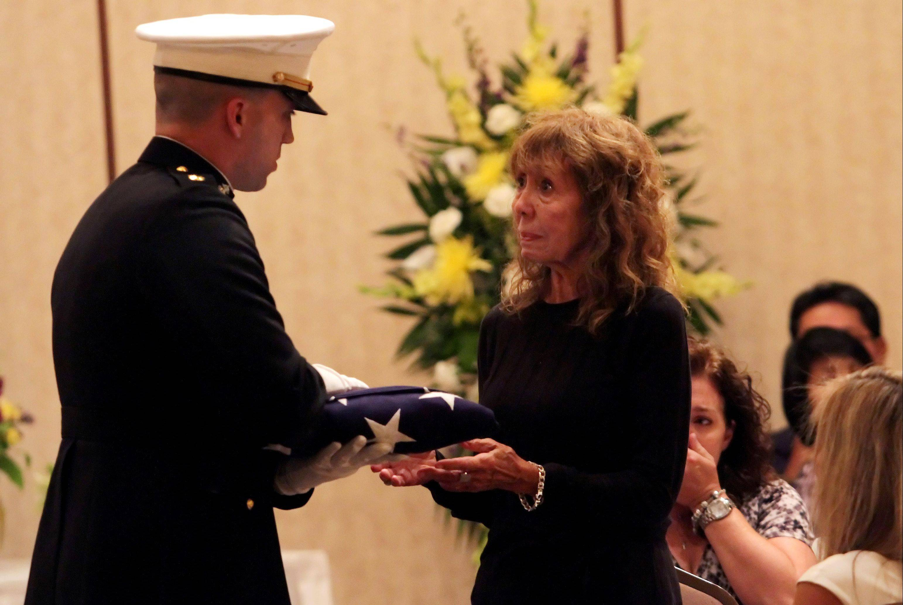 Caroll Suchy receives a flag from a member of the U.S. Marine Corps Reserve Center in Joliet during a memorial ceremony Thursday evening in Willowbrook for her son Randy Suchy, 59, of Naperville. He died Friday while helping to save a 12-year-old boy from drowning.