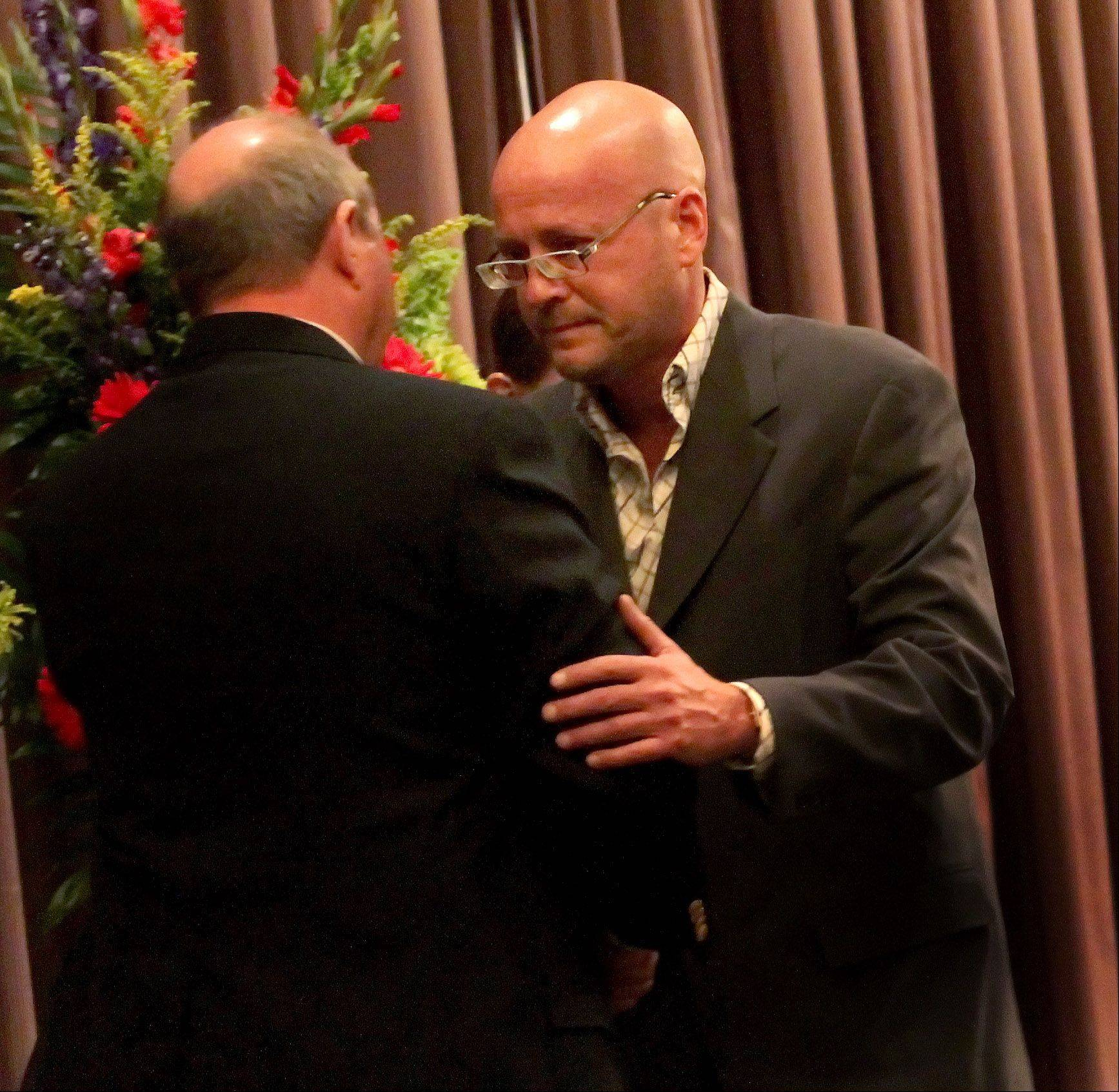 Steven Grubert of Downers Grove hugs Julio D'Alessandro, left, of St. Charles after both spoke during a memorial ceremony Thursday in Willowbrook for Grubert's cousin Randy Suchy of Naperville. Randy died Friday while saving a 12-year-old boy from drowning.