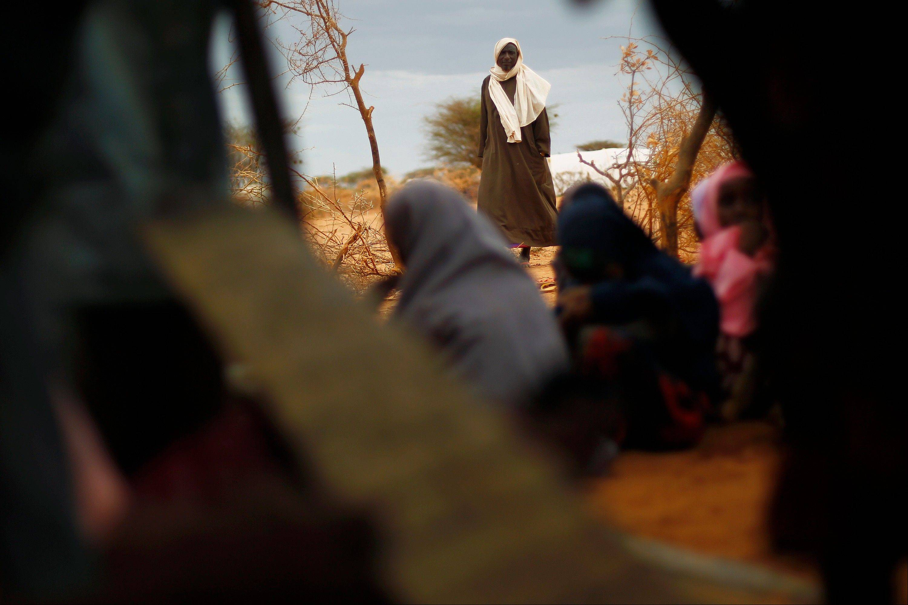 A Somali refugee looks at pupils studying the Koran at an outdoor madrasa at the Ifo camp outside Dadaab, Eastern Kenya, 100 kms (60 miles) from the Somali border, Tuesday Aug. 9, 2011. U.S. President Barack Obama has approved $105 million for humanitarian efforts in the Horn of Africa to combat worsening drought and famine. The drought and famine in the Horn of Africa has killed more than 29,000 children under the age of 5 in the last 90 days in southern Somalia alone, according to U.S. estimates. The U.N. says 640,000 Somali children are acutely malnourished, suggesting the death toll of small children will rise.