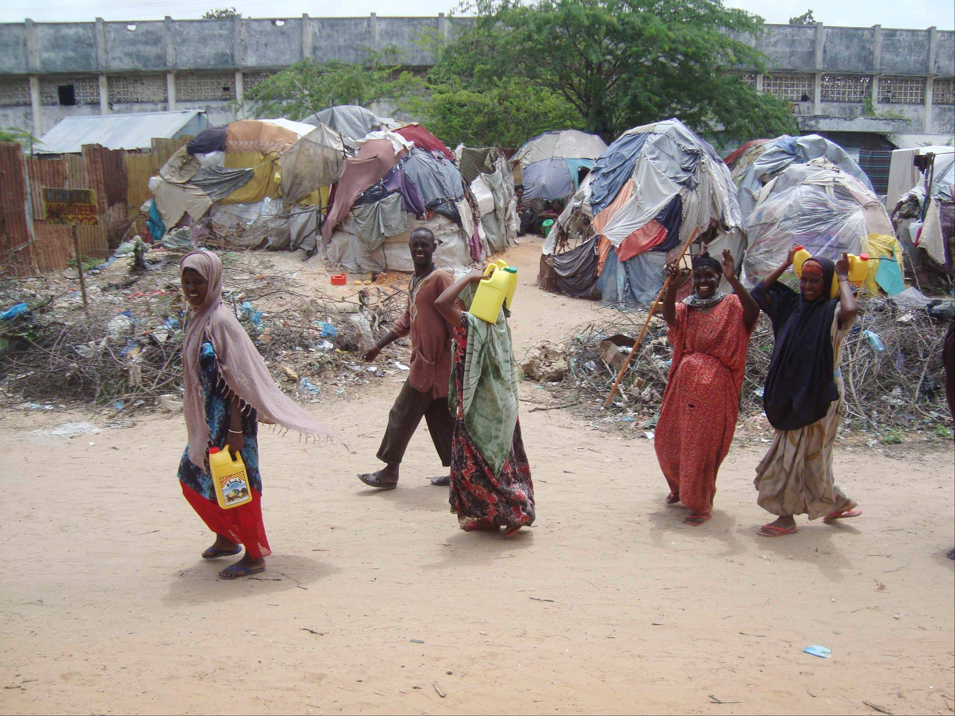 Southern Somali people carrying rations from a food distribution centre toward a refugee camp in Mogadishu, Somalia, Thursday, Aug. 11, 2011. The drought and famine in Somalia have killed more than 29,000 children under the age of 5, according to U.S. estimates, the first time such a precise death toll has been released, and the U.N. says 640,000 Somali children are acutely malnourished, a statistic that suggests the death toll of small children will rise.