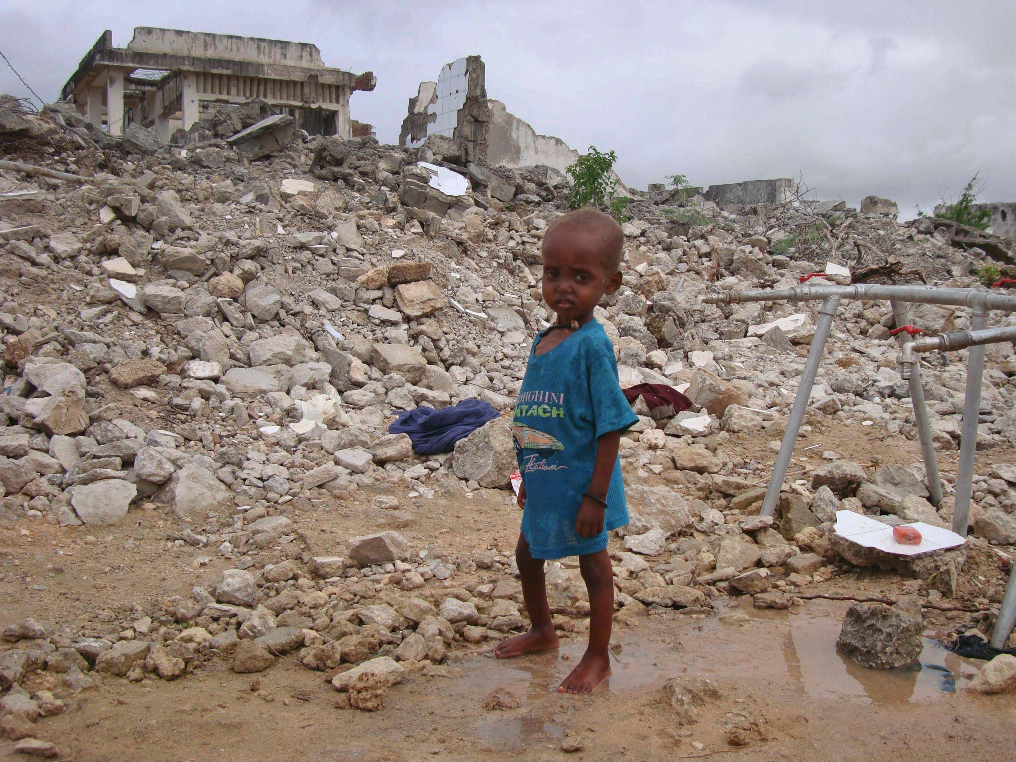 A Somali child from southern Somalia stands in the rubble of a destroyed building near a refugee camp in Mogadishu, Somalia, Tuesday, Aug 9, 2011. The number of people fleeing famine-hit areas of Somalia is likely to rise dramatically and could overwhelm international aid efforts in the Horn of Africa, a U.N. aid official said Tuesday.