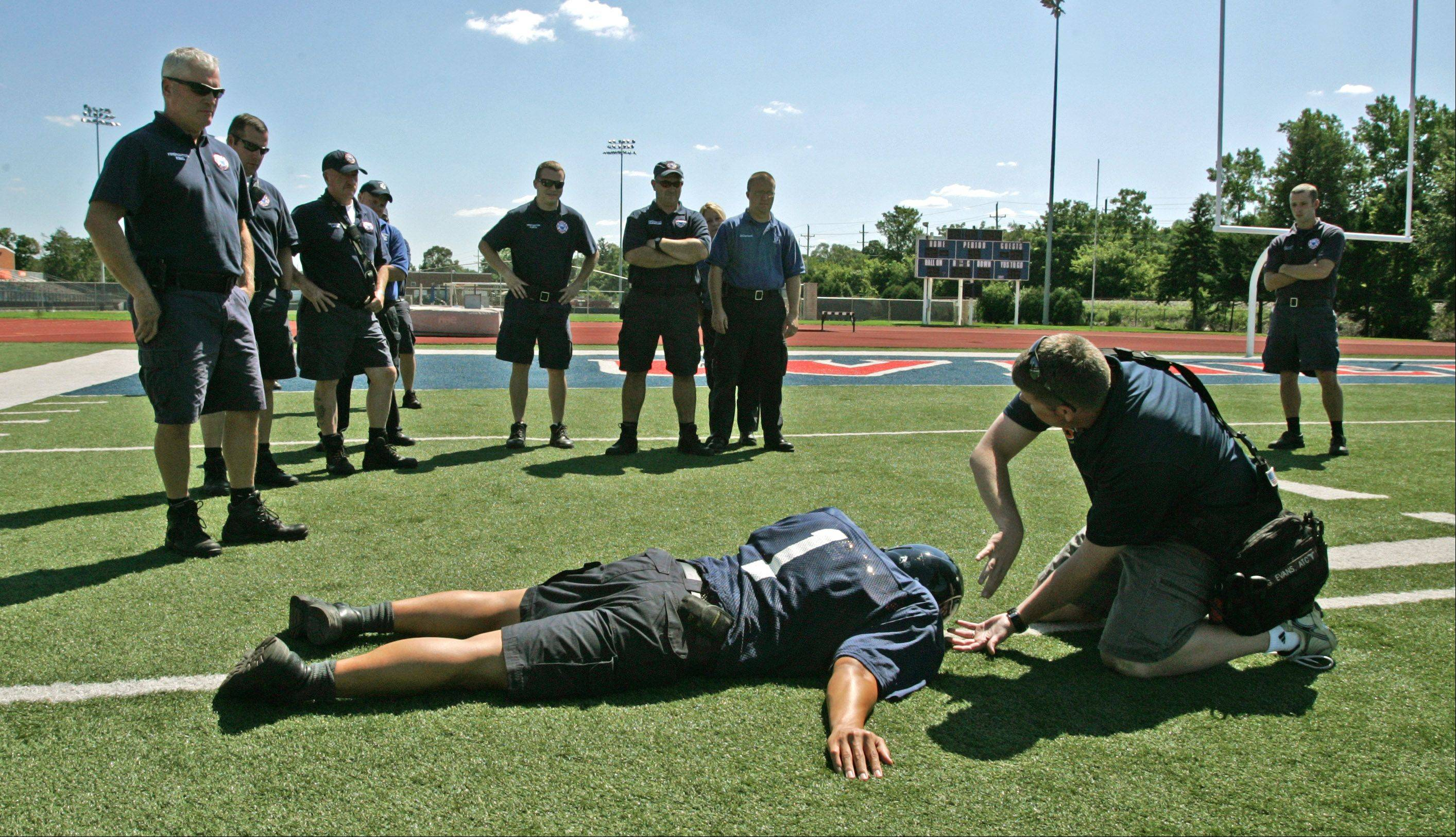 Wheaton College head athletic trainer Greg Evans, right, talks to Wheaton Fire Department personnel about moving spinal injury patients. Firefighter Willie Cox poses as an injured football player during the once-a-year refresher course.