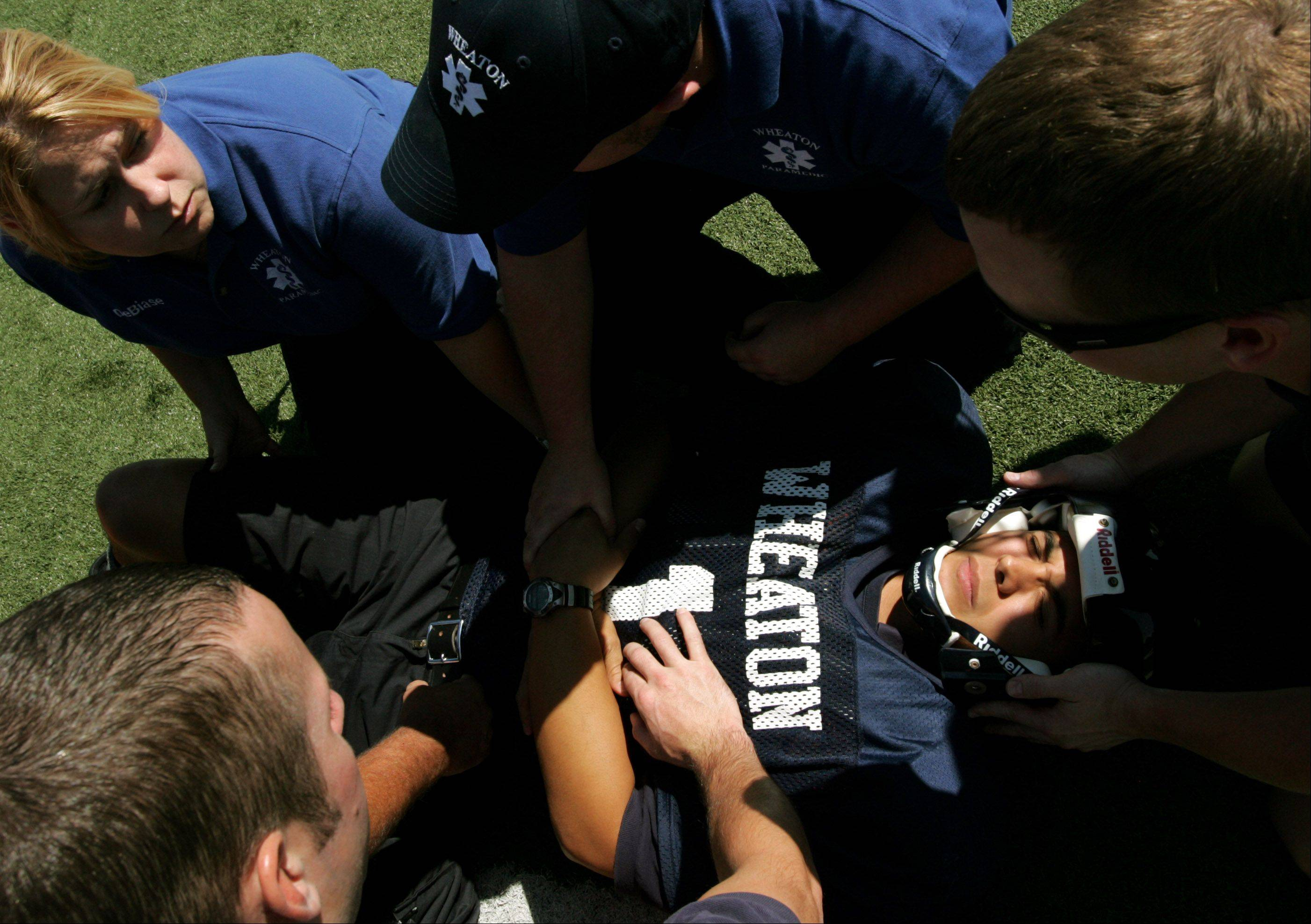 Wheaton firefighter Willie Cox poses as an injured football player during a training exercise on spinal injuries at Wheaton College. Cox said the exercise gave him a patient's perspective.