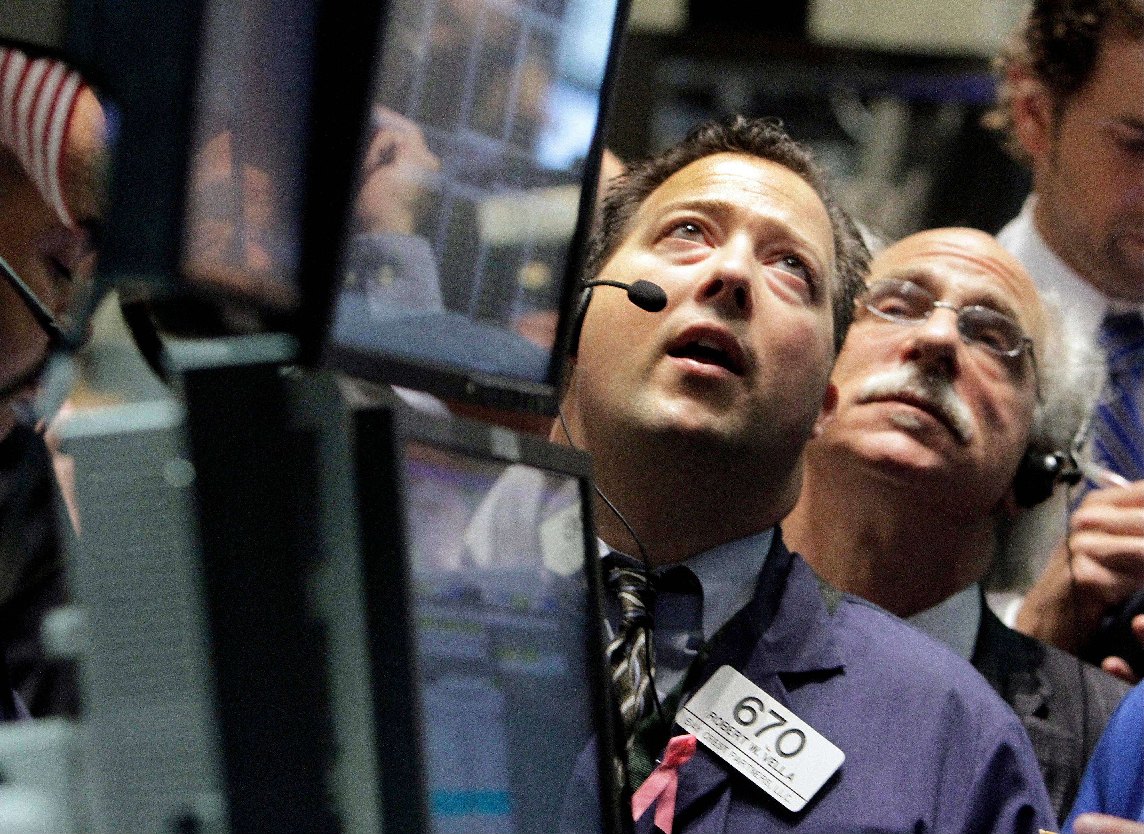 Traders Robert Vella, left, and Peter Tuchman work on the floor of the New York Stock Exchange Thursday.