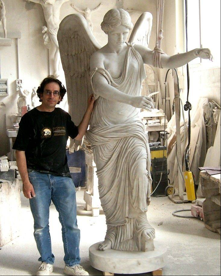 "Renowned stone carver Walter Arnold, shown here in his studio with his work, ""Vittoria Alata"" or ""Roman Winged Victory,"" has his gargoyles and Gothic sculptures on display at Elgin's Gail Borden Public Library. The display is in keeping with the library's Medieval summer theme, ""A Midsummer Knight's Read."""