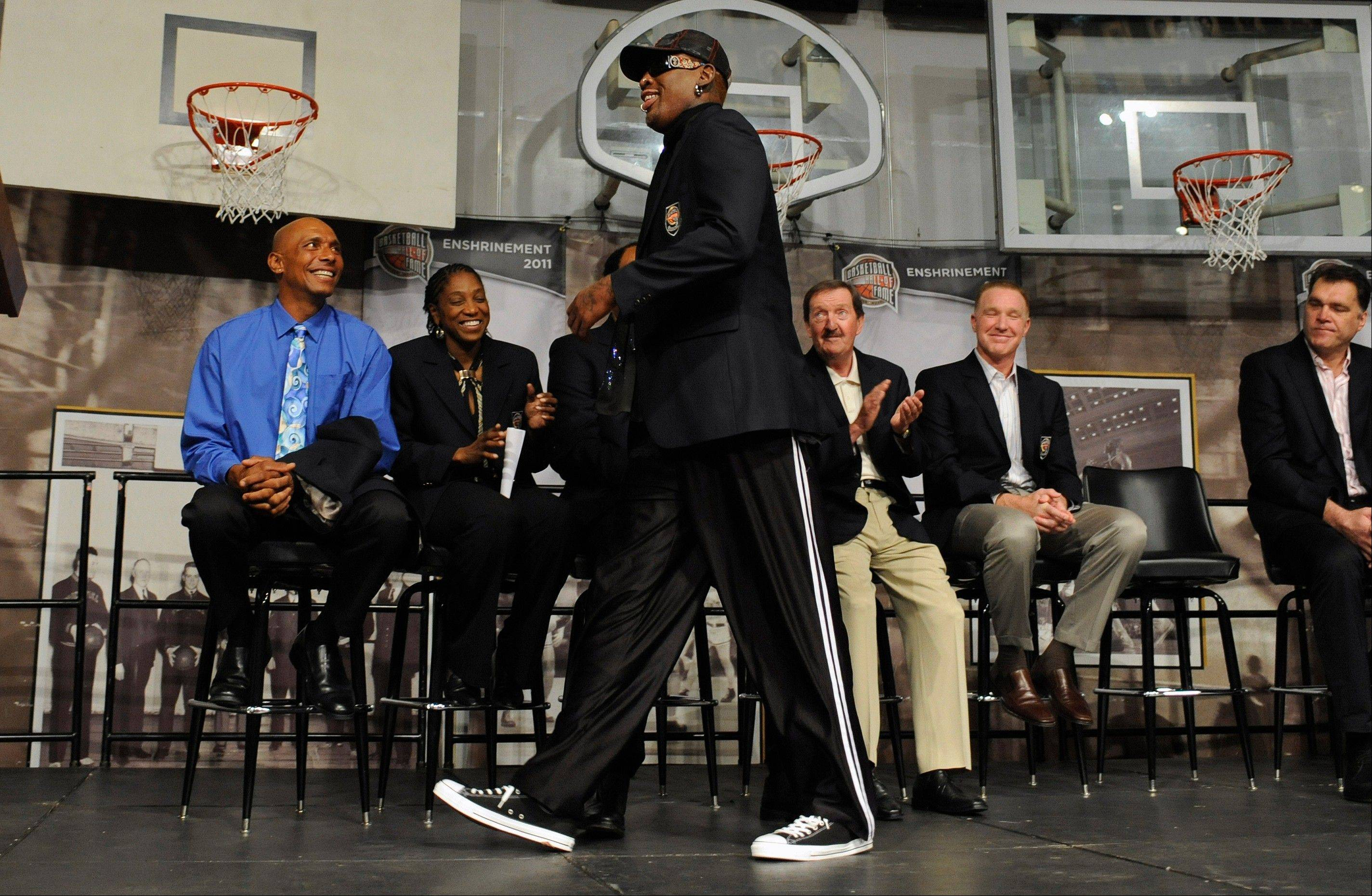 Dennis Rodman walks past fellow future inductees into the Basketball Hall of Fame during a news conference at the Naismith Memorial Basketball Hall of Fame in Springfield, Mass., Thursday, Aug. 11, 2011.