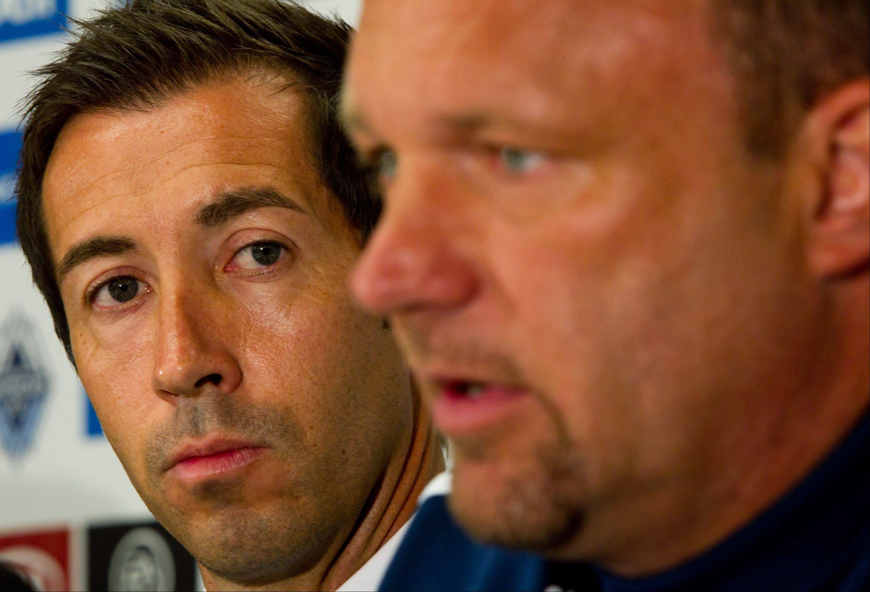 Martin Rennie, left, of Scotland, listens as Vancouver Whitecaps' acting head coach Tom Soehn speaks during a news conference in which Rennie was introduced as the new coach of the soccer team in Vancouver, British Columbia, on Tuesday. Soehn, the club's director of hockey operations, will hand over the coaching duties to Rennie at the end of the season. Soehn, a graduate of Forest View High School in Arlington Heights, once played for the Chicago Fire.