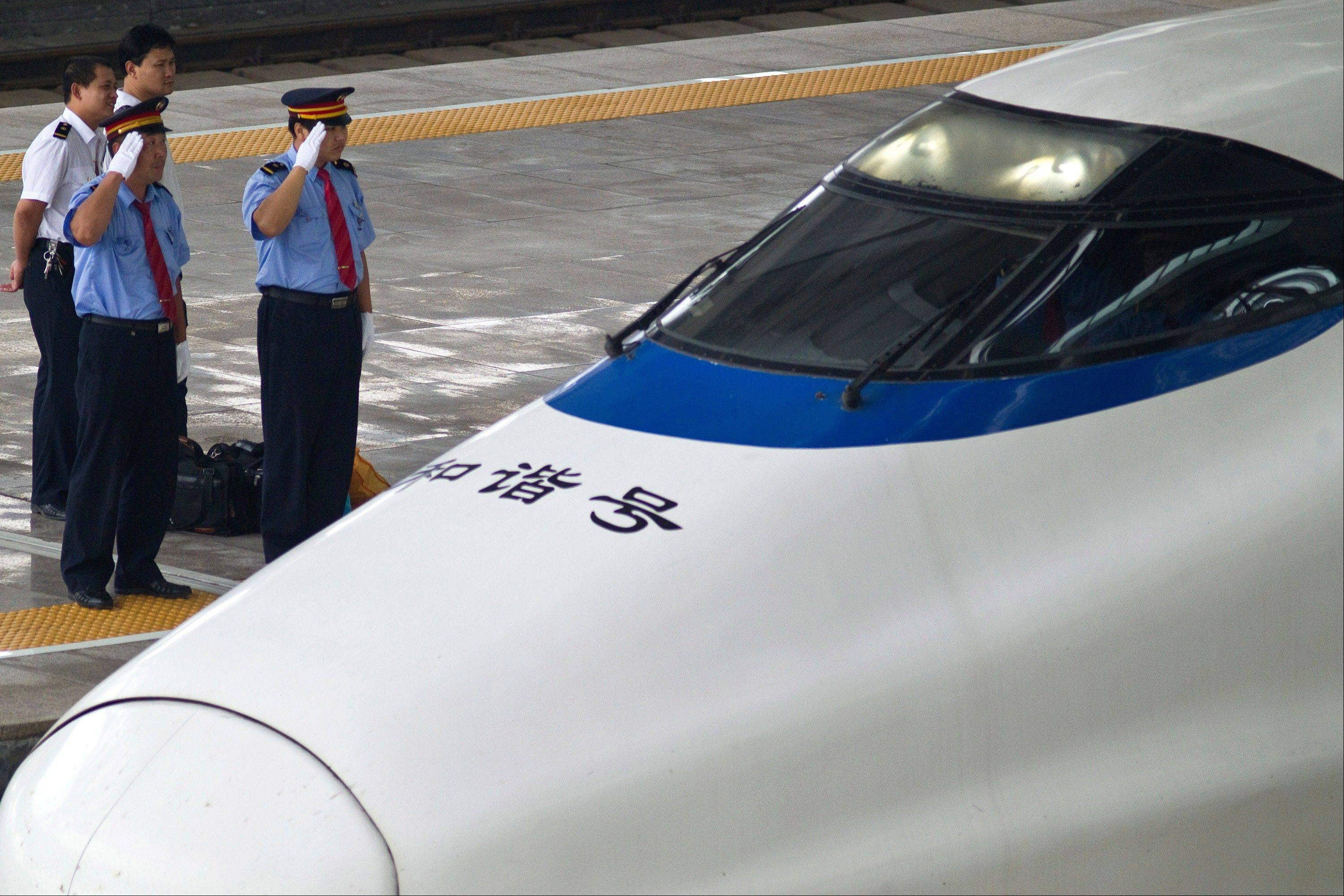 Train drivers salute as a CRH high-peed train arrives at Beijing South Station in Beijing Friday.