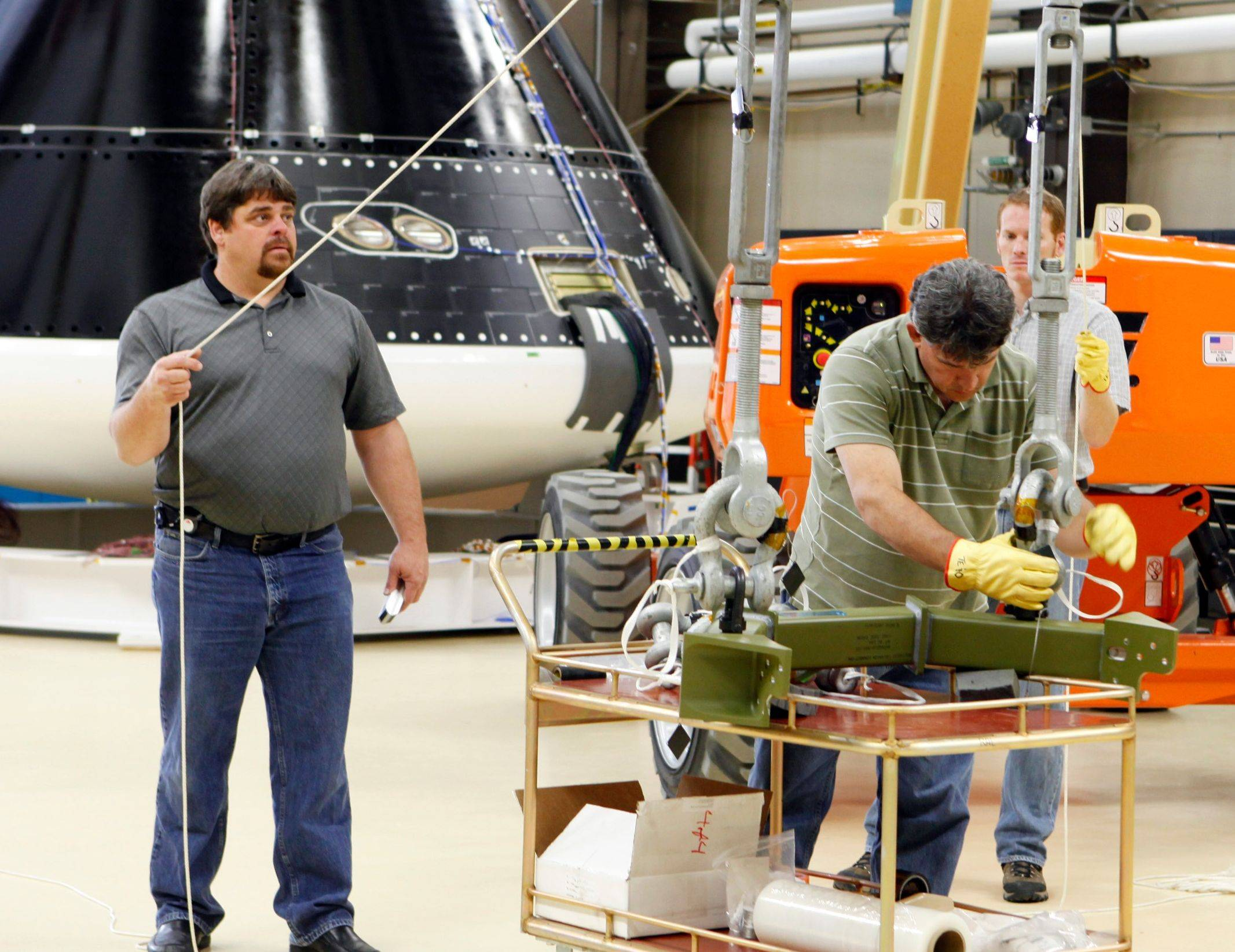 Engineers work on the Orion spacecraft Friday at the Lockheed Martin facility in Denver. Vibration testing on the spacecraft is expected to get underway today.