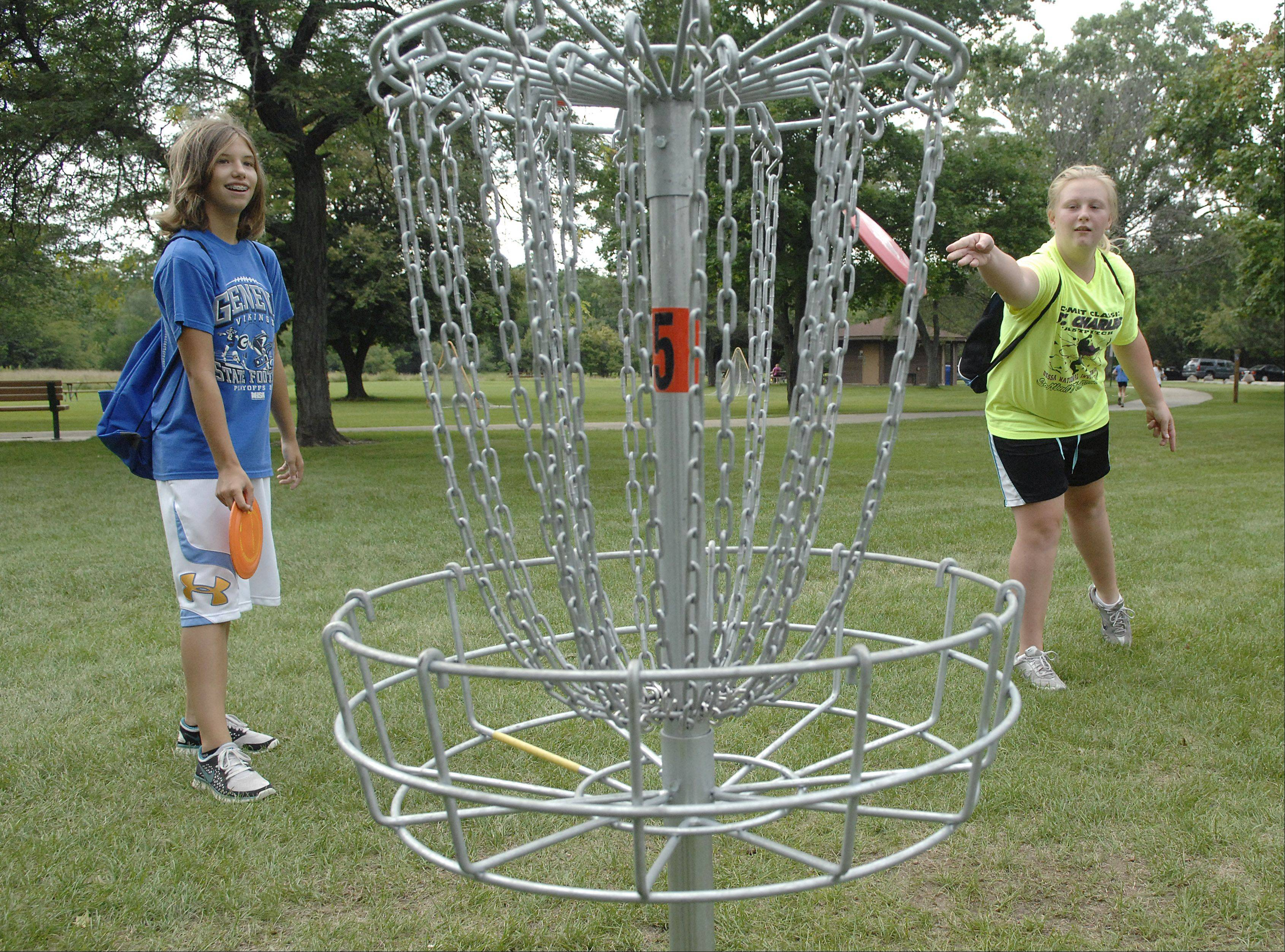 Elizabeth Ariss, 13, left, and Jennifer Cale, 14, both of Geneva have been coming to the new disc golf course at Wheeler Park in Geneva about four times a week the past two weeks.