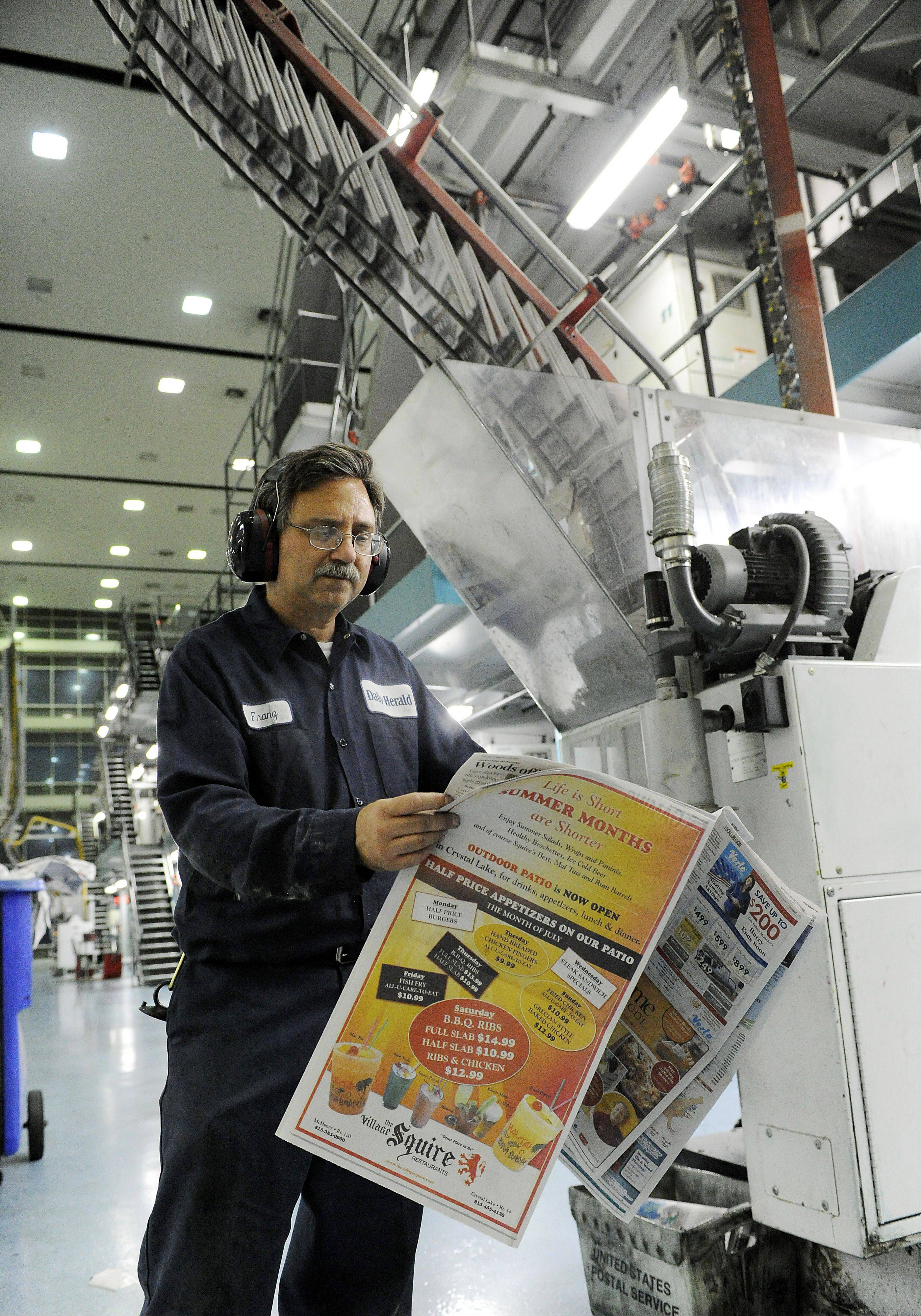 Pressman Franz Sinkovits inspects the Daily Herald for color, registration errors and overall quality.