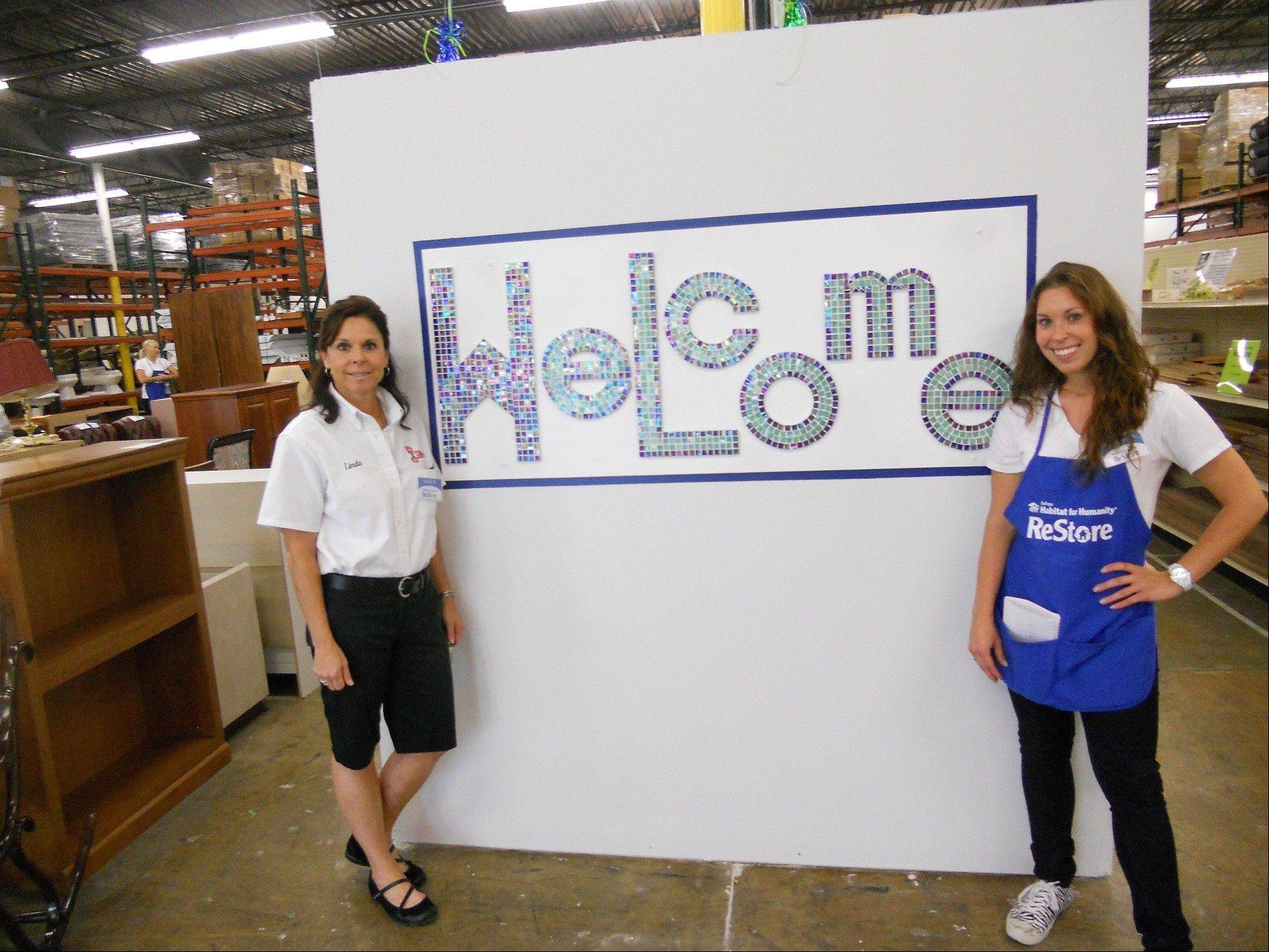 Linda DiStefano, left, and her daughter, Vanessa, debut their mosaic-tiled welcome sign at DuPage Habitat ReStore in Addison.
