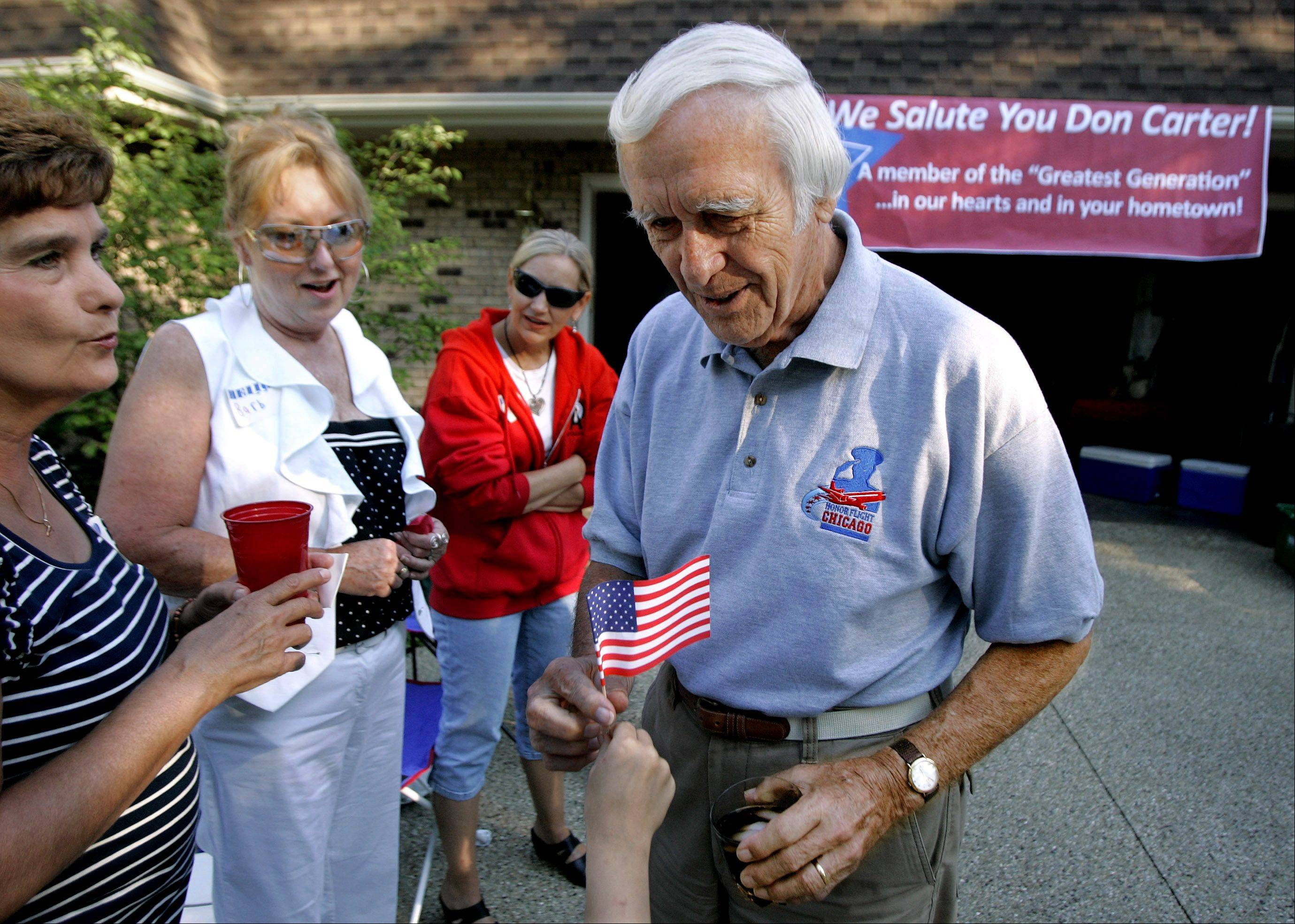 WWII veteran Donald Carter receives an American flag as he attends a surprise block party in his honor Thursday in Libertyville. Carter returned recently from an Honor Flight to Washington D.C.